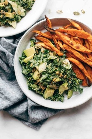 Avocado Kale Caesar Salad on a plate with sweet potato fries.