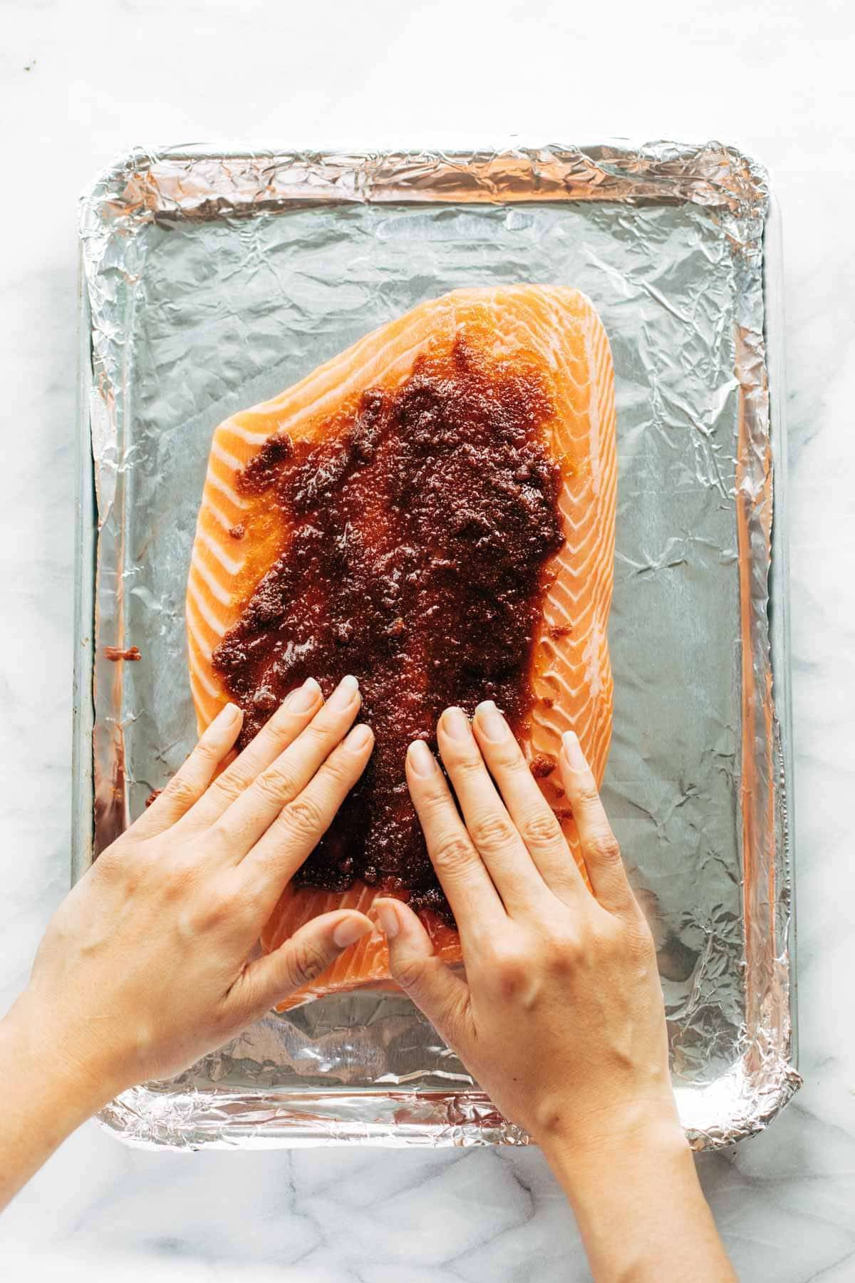 Adding rub to salmon on sheet pan.