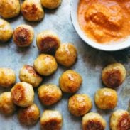 Baked Chicken Meatballs on a sheet pan with sauce.