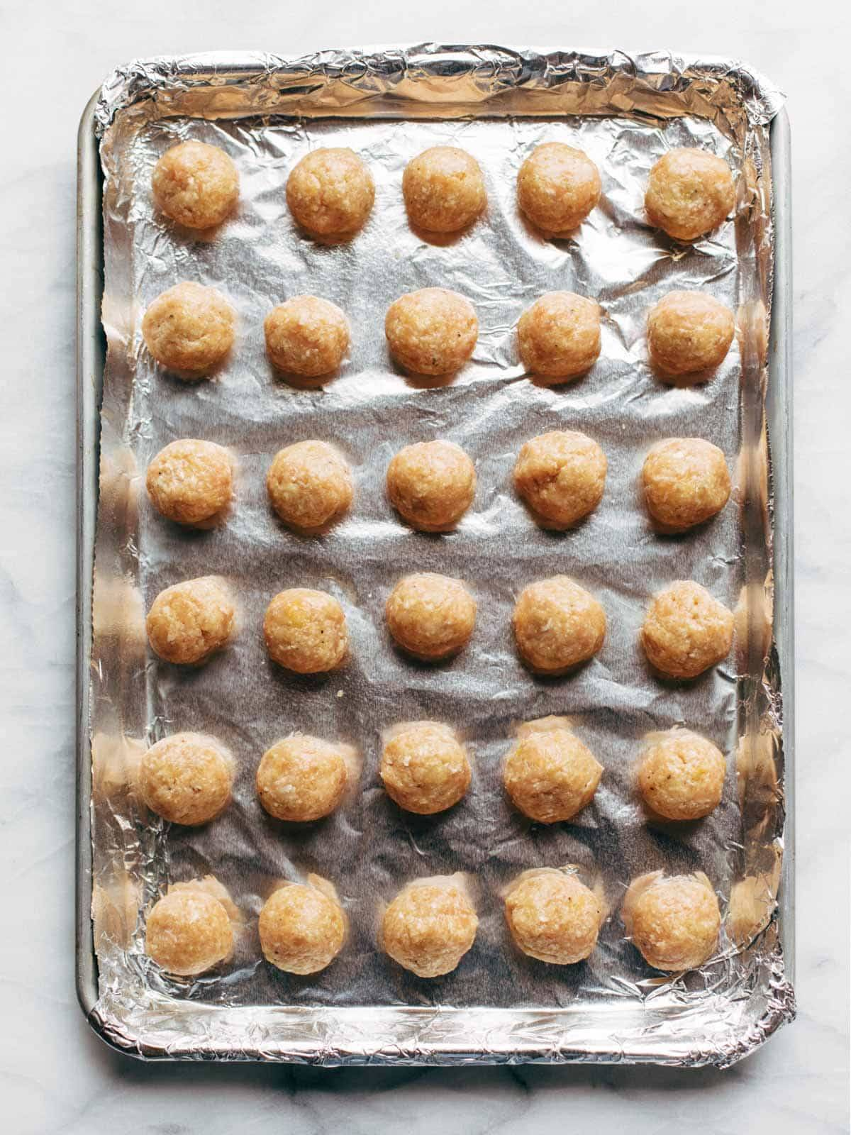 Unbaked Chicken Meatballs on a sheet pan.