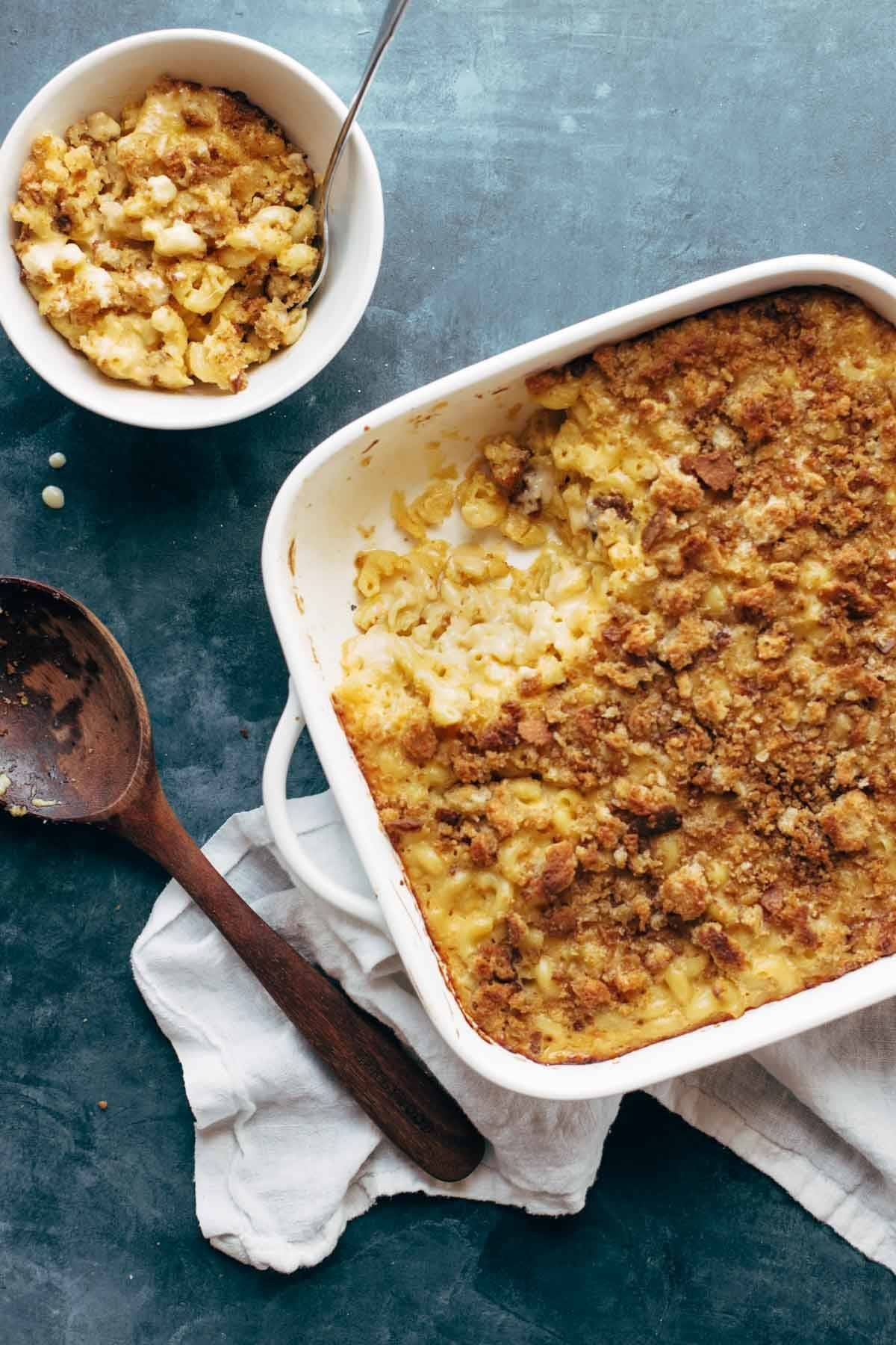Baked Mac and Cheese in a dish with a wooden spoon and a bowl of mac and cheese on the side