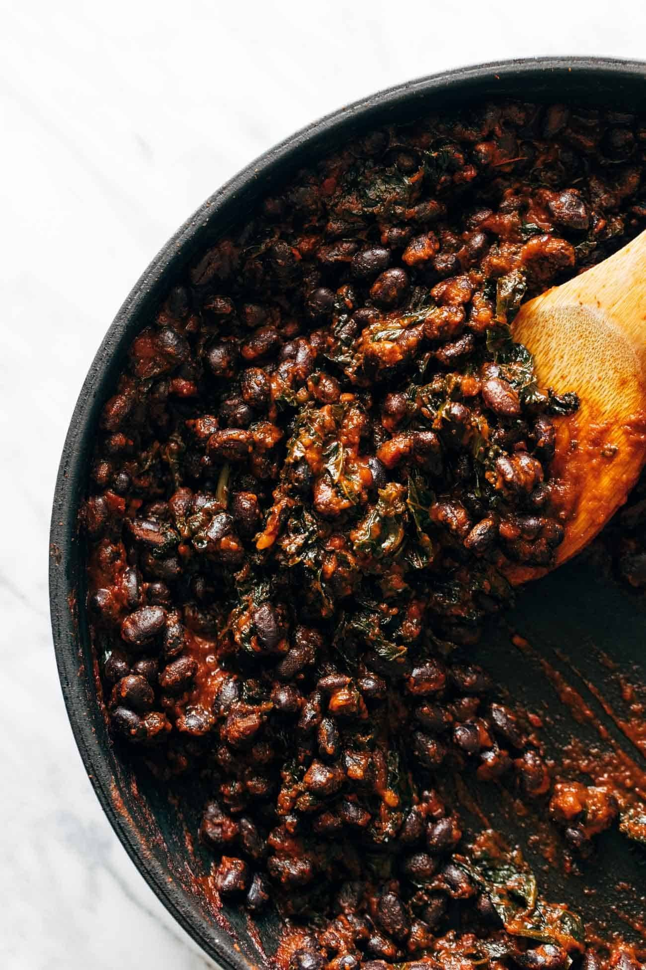 Smoky black bean filling with greens being stirred around in a pan with a wooden spoon.