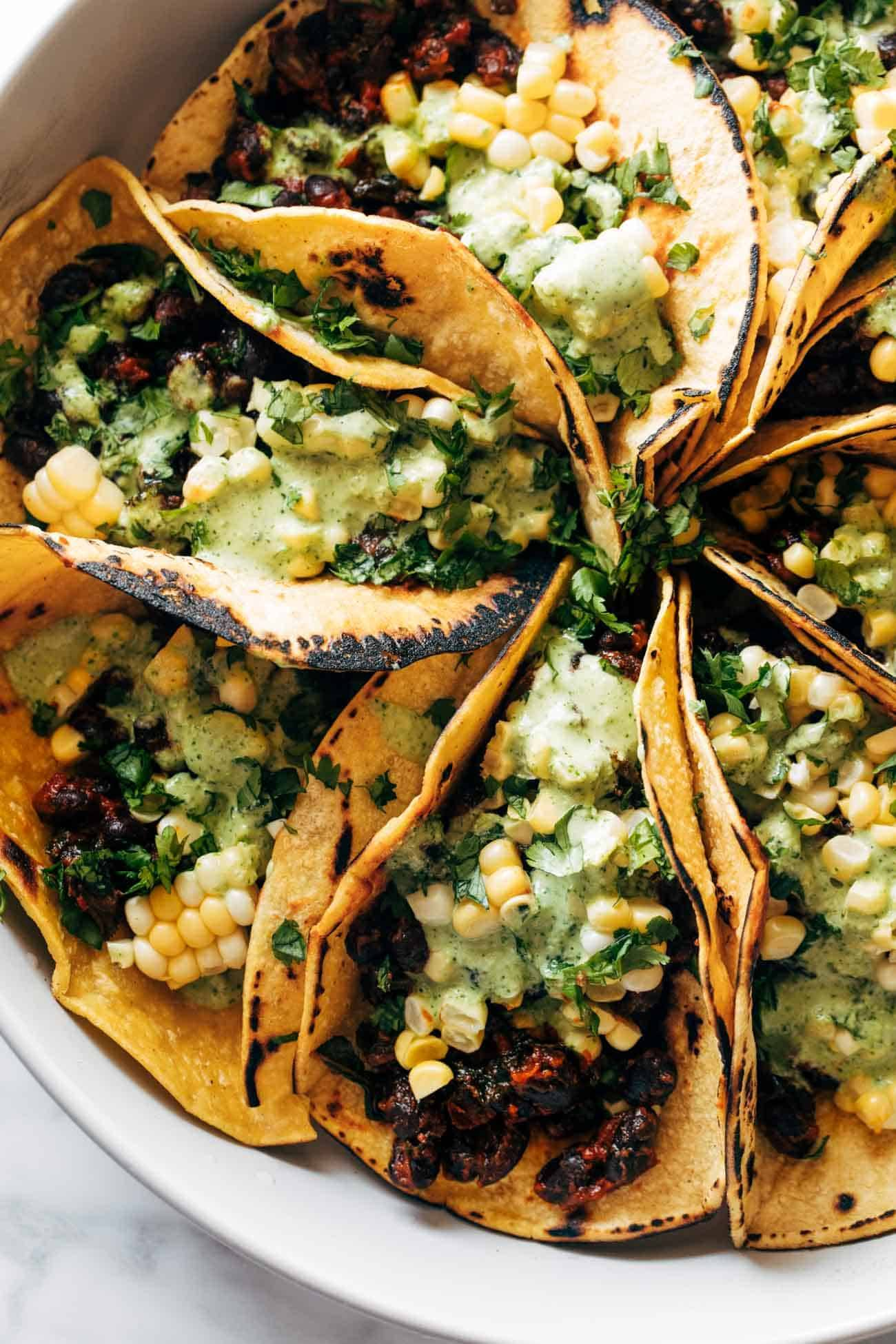 Smoky beans and greens tacos tucked together in a pan and topped with corn and Aji Verde sauce.