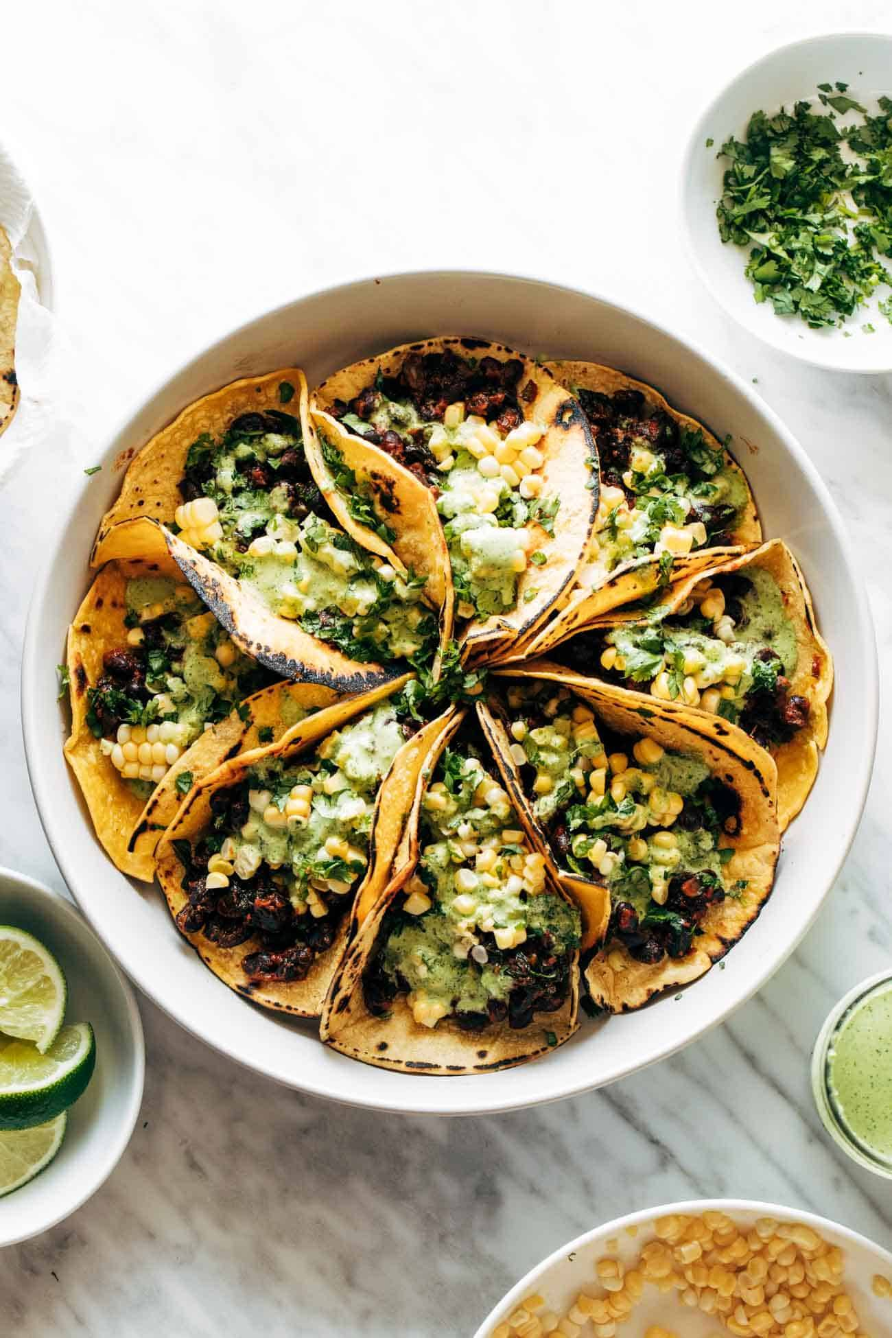 Smoky beans and greens tacos in a circular pattern on a plate and topped with Aji Verde sauce and corn.