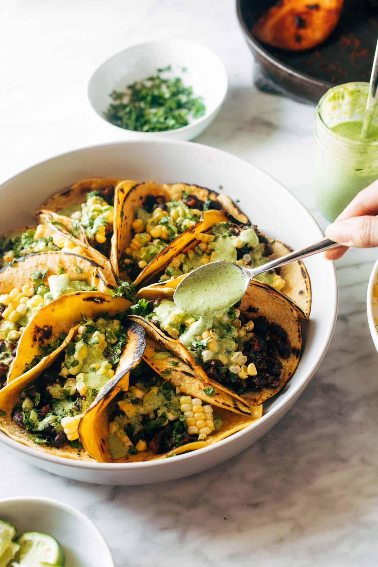 Smoky beans and greens tacos on a plate with corn and aji verde sauce being drizzled on top with a metal spoon.