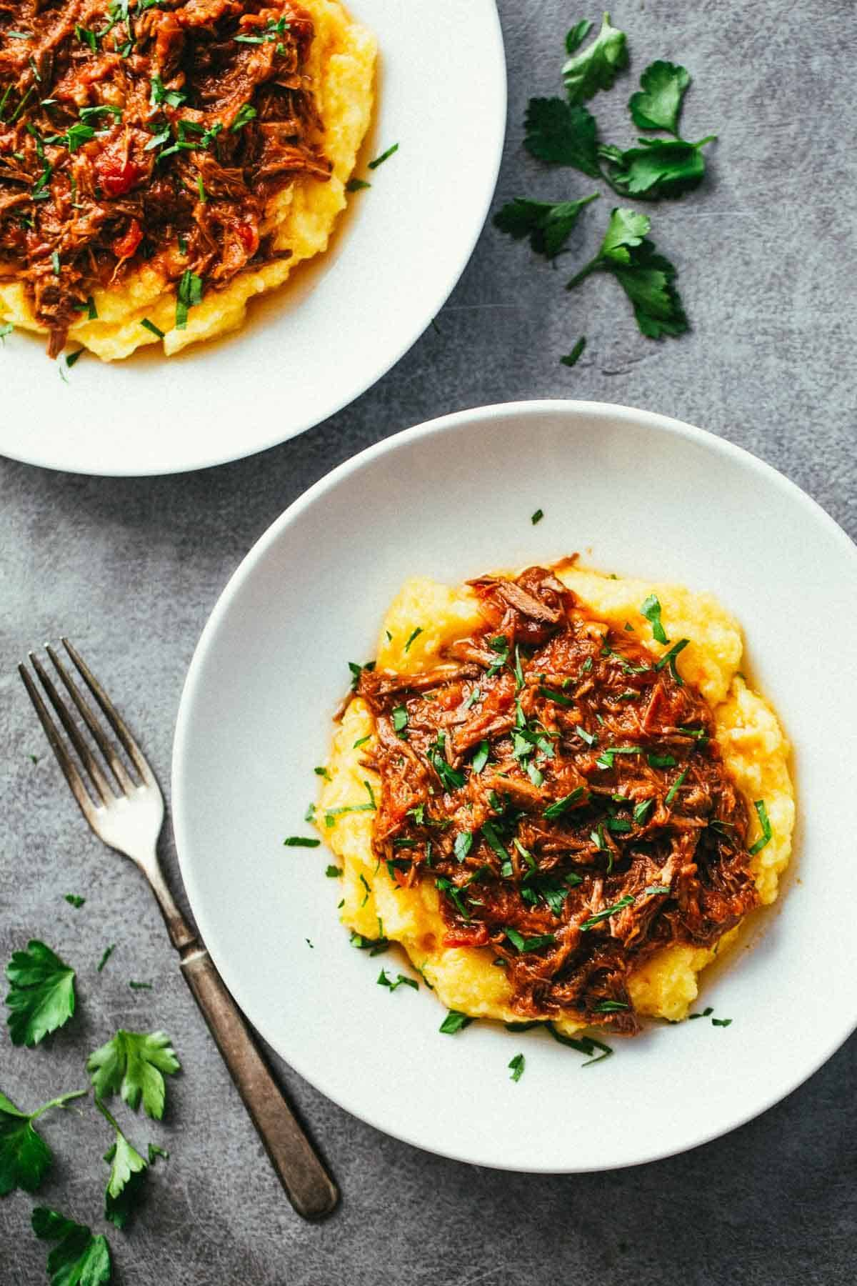 Crockpot Braised Beef Ragu with Polenta on two white plates.