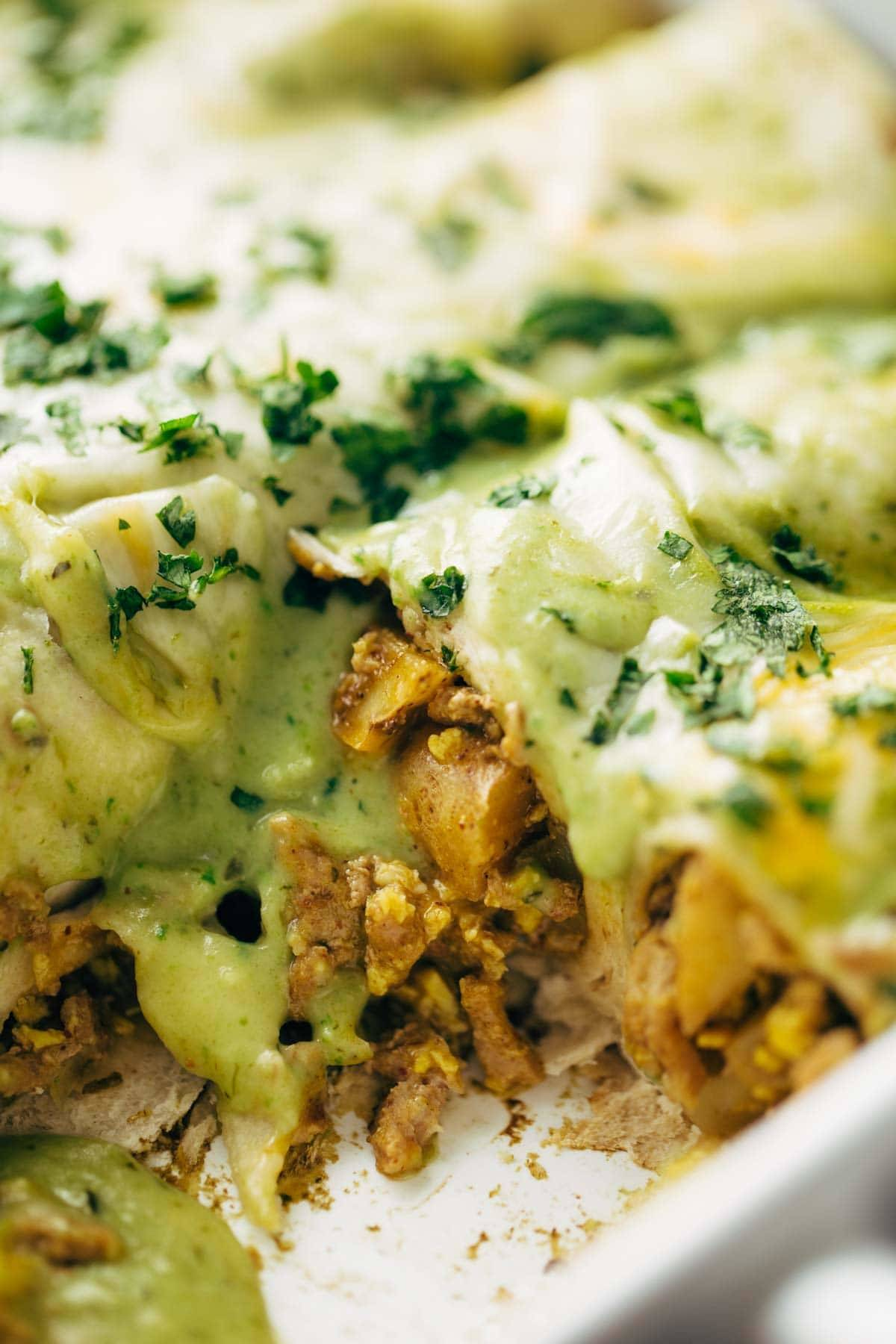 Breakfast Enchiladas - with scrambled eggs, chili potatoes, spicy turkey, cheese, and a homemade roasted poblano sauce. SUPER yummy! Love this recipe for breakfast, brunch, or brinner. | pinchofyum.com