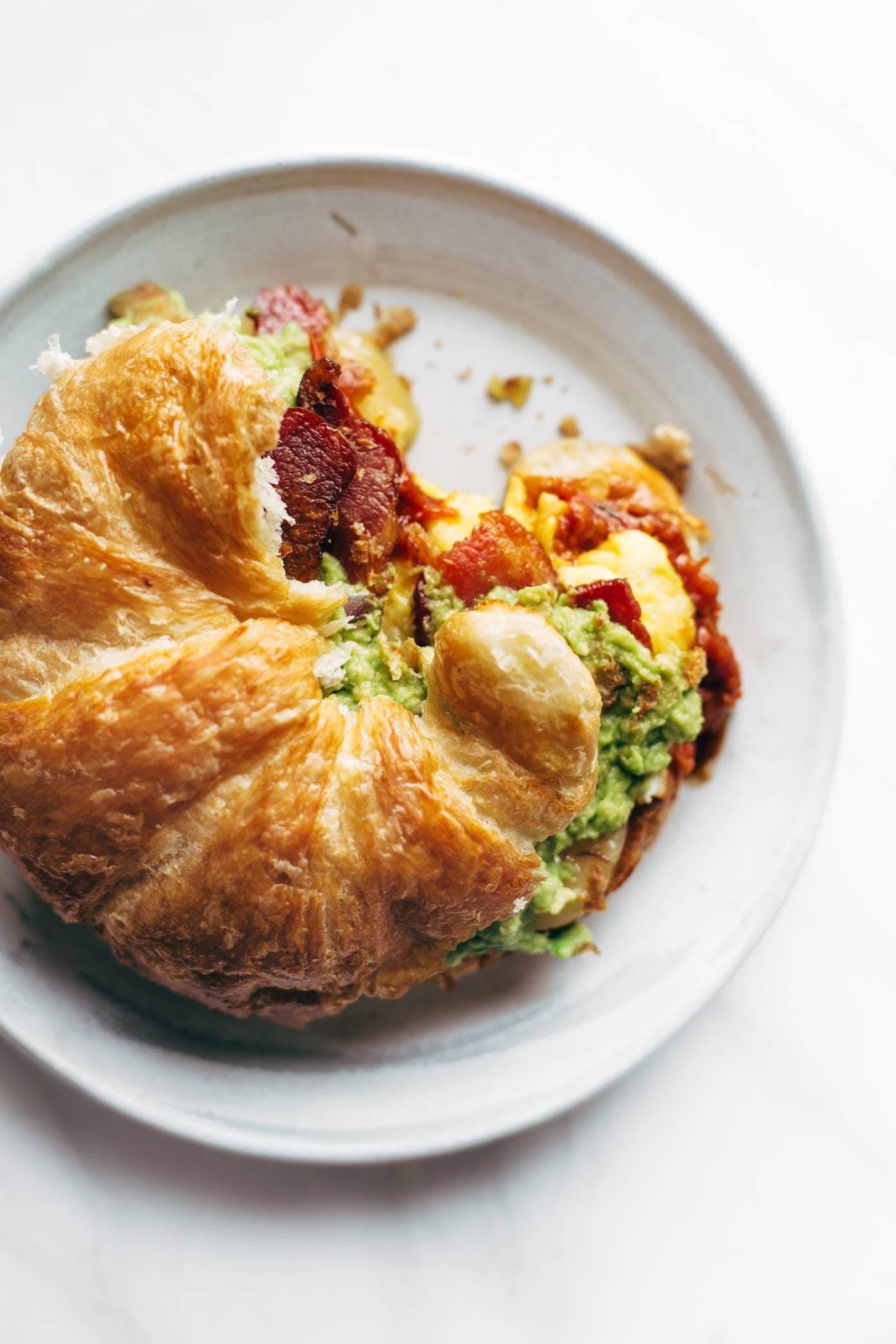 The Ultimate Breakfast Sandwich with eggs, bacon, guacamole, chunky tomato sauce, pepper jack cheese, all on a toasted croissant. 😍 Favorite ever. | pinchofyum.com