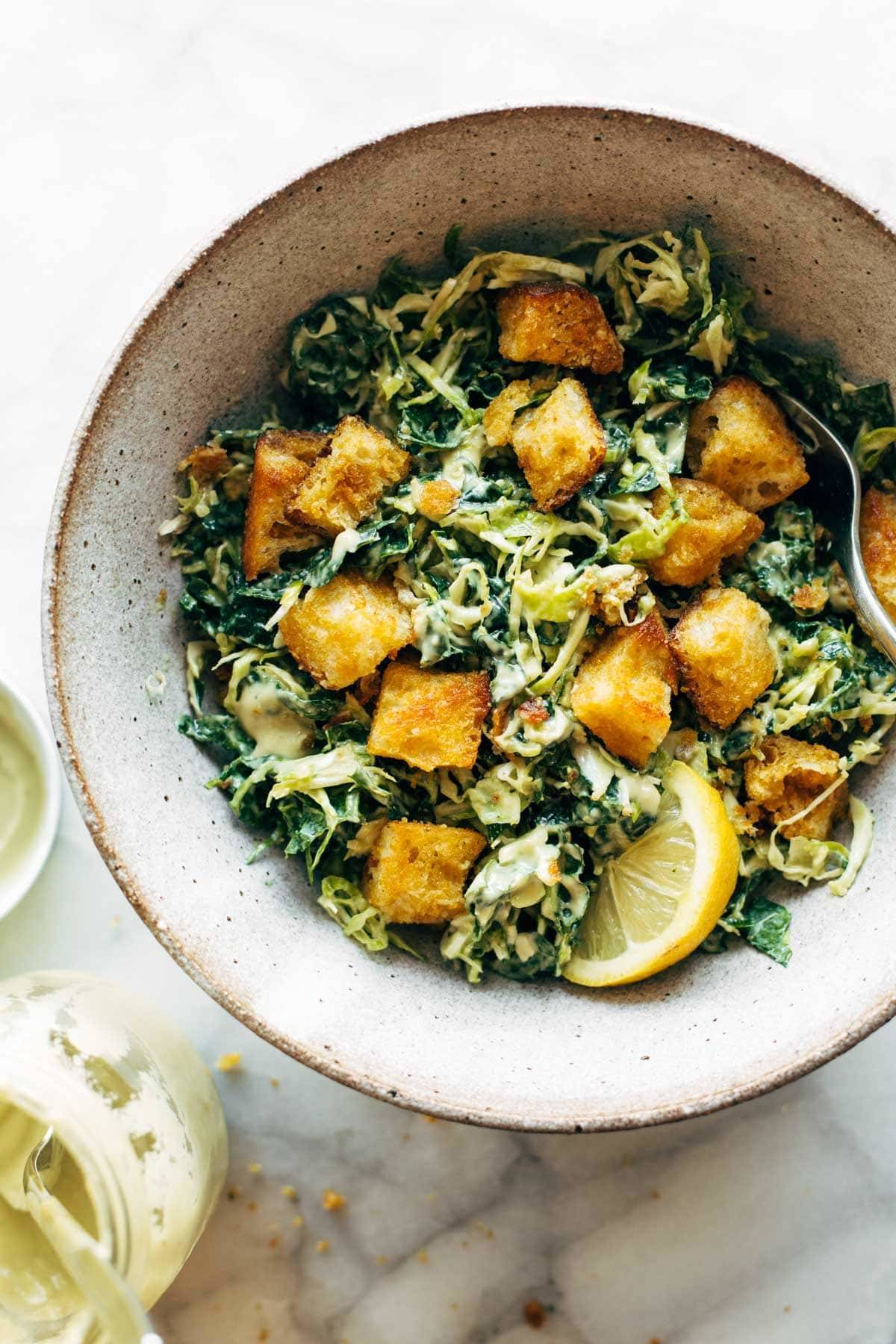 Brussels & Kale Caesar in a bowl with Cheezy Garlic Croutons.