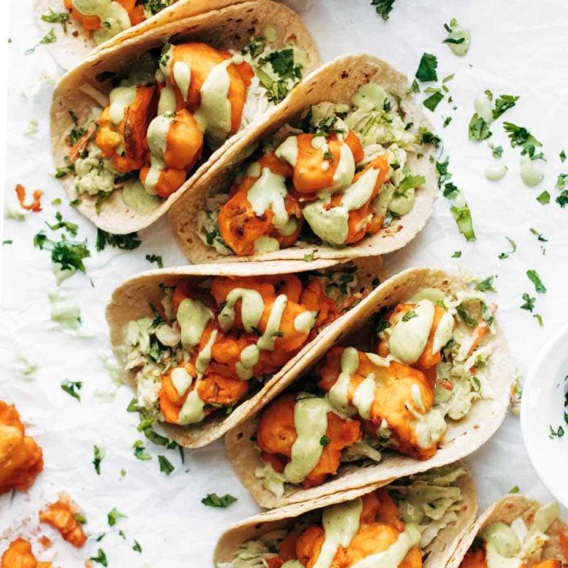 Buffalo Cauliflower Tacos on table in a row.