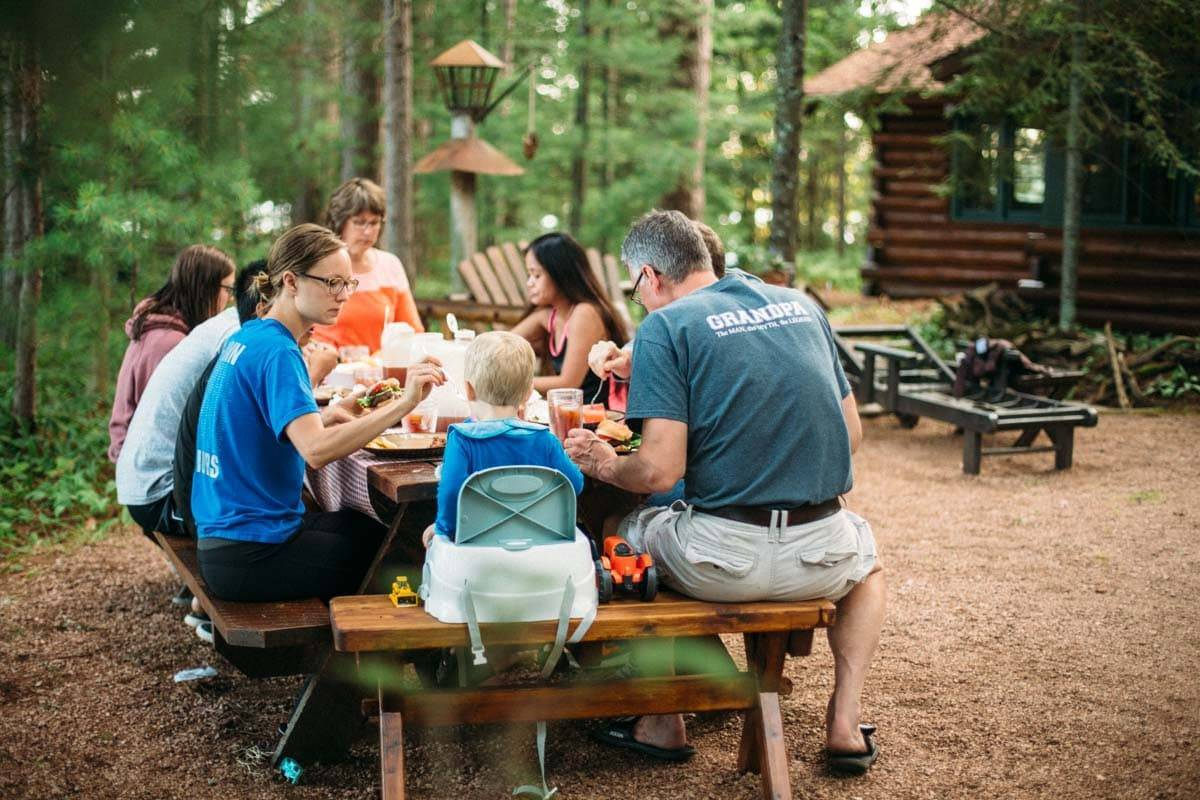 People sitting around a table at a cabin eating.