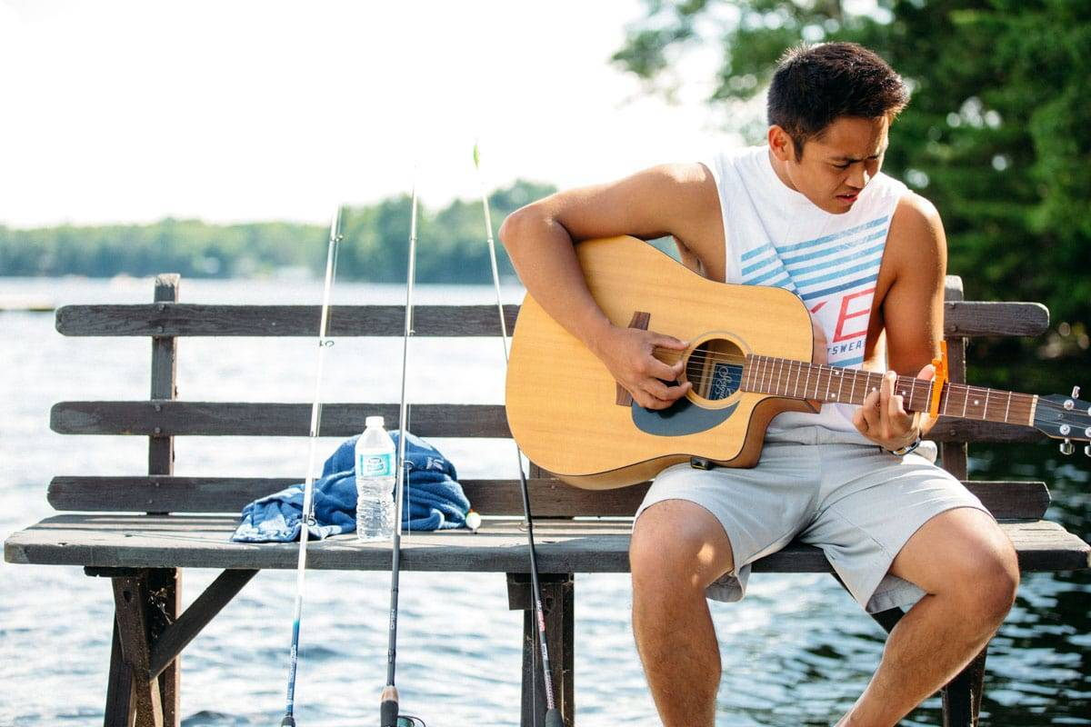 Boy playing guitar on a dock.