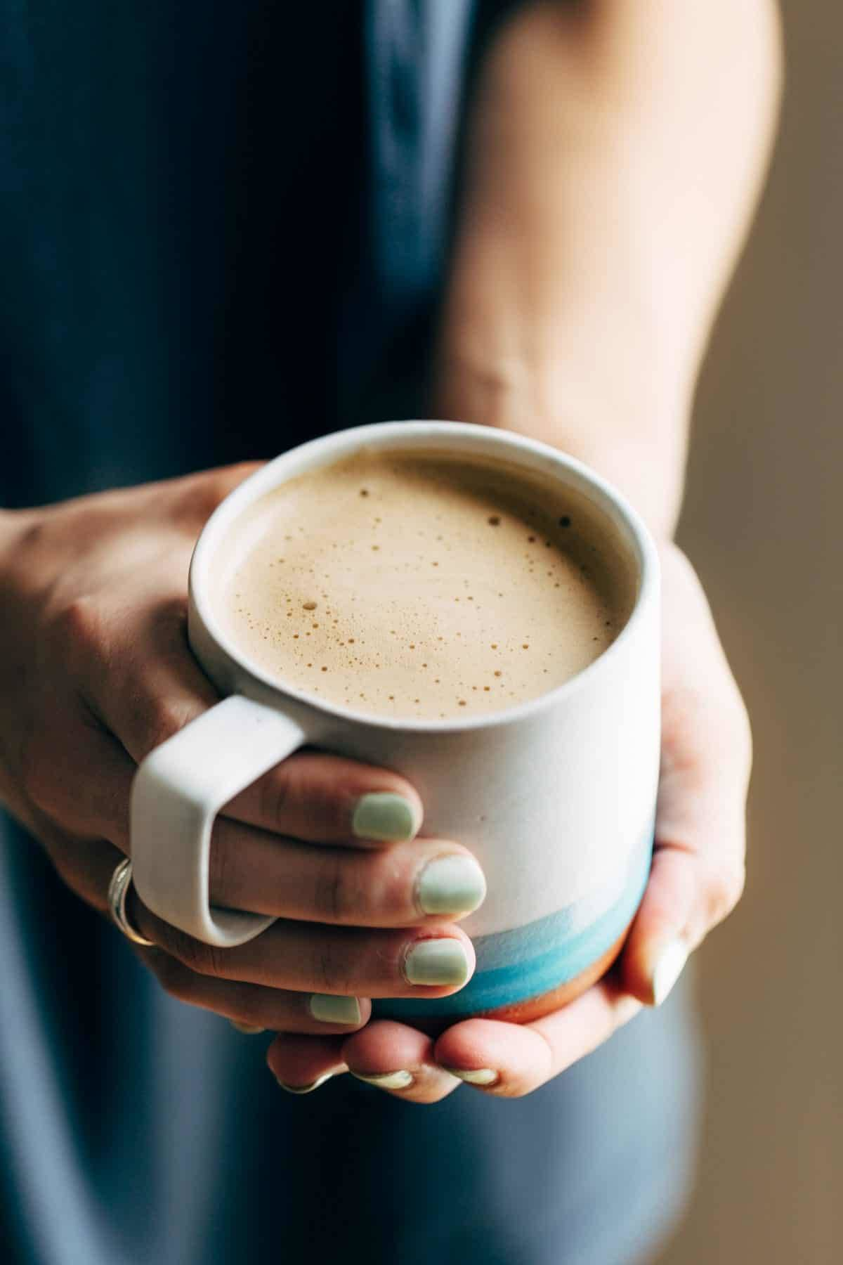Hands holding a mug of Cashew Coffee.