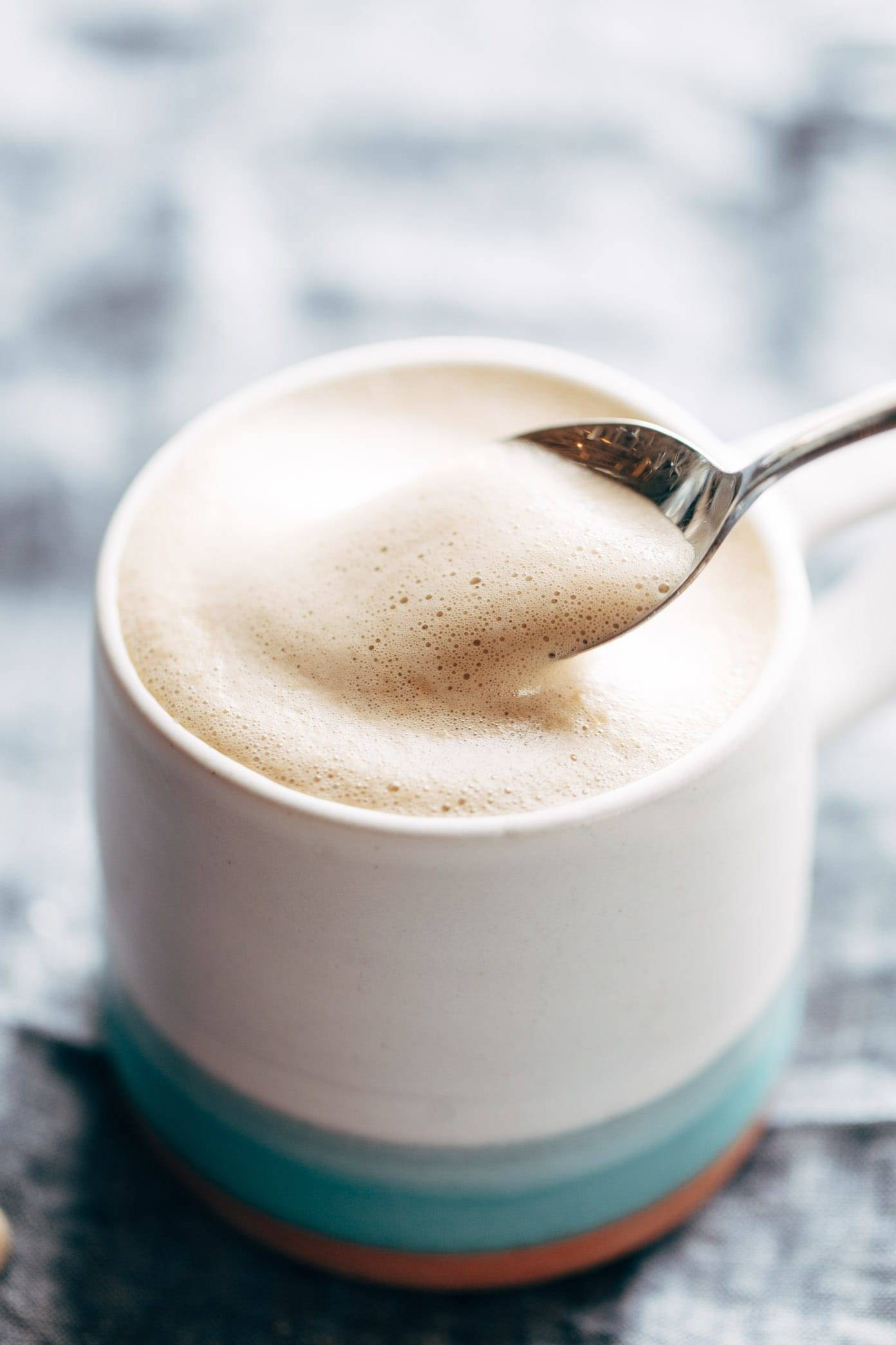 Cashew Coffee in a mug with foam on a spoon.