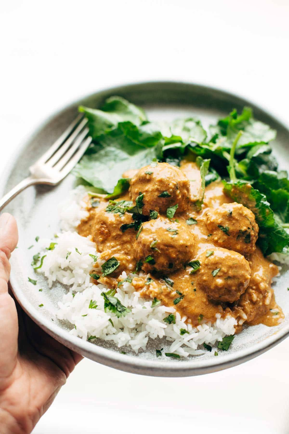White hand holding a plate with cauliflower vegetarian meatballs, white rice, and fresh herbs sprinkled on top. There is a fork on the plate with greens.