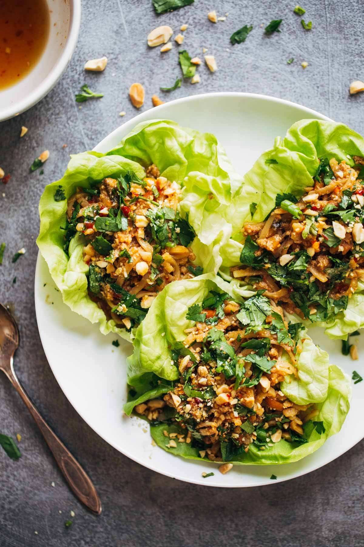 Peanut Chicken Lettuce Wraps with a Ginger Garlic sauce on a white plate.