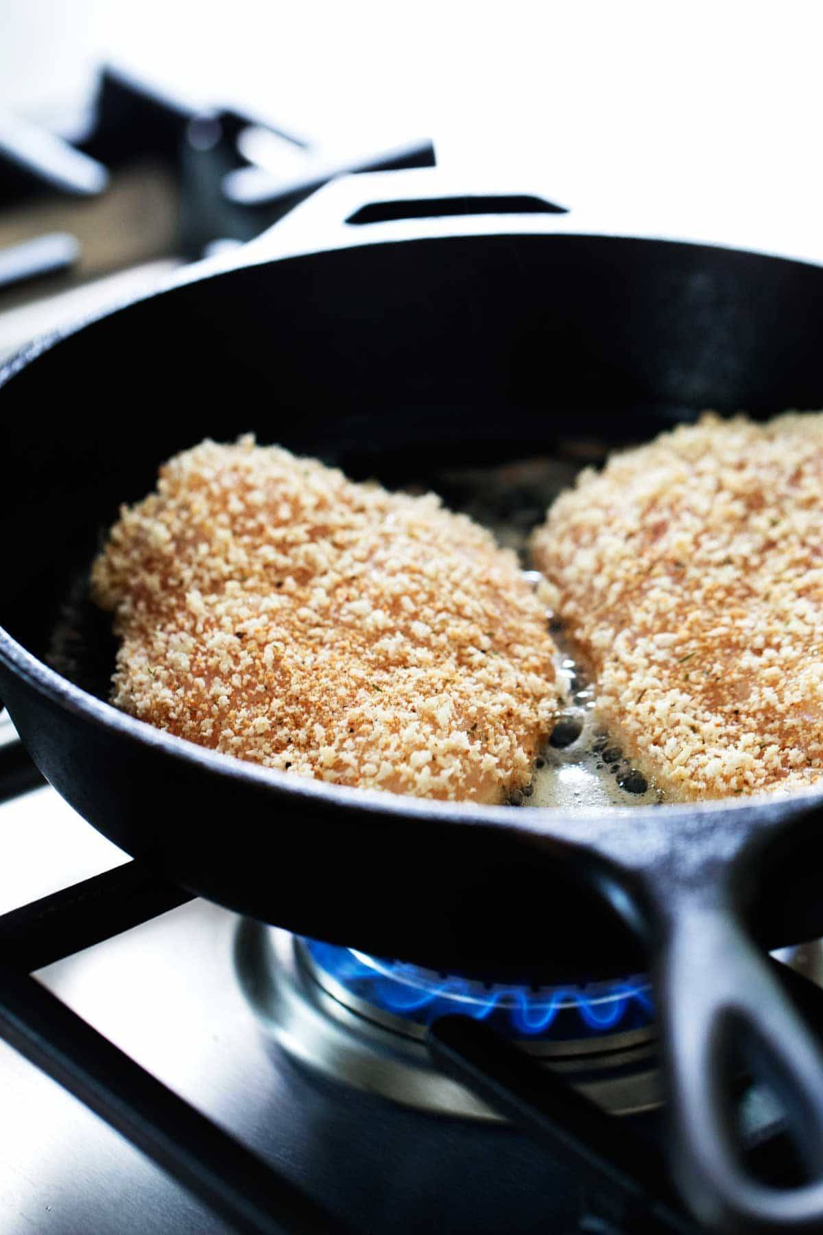Breaded chicken on a skillet.