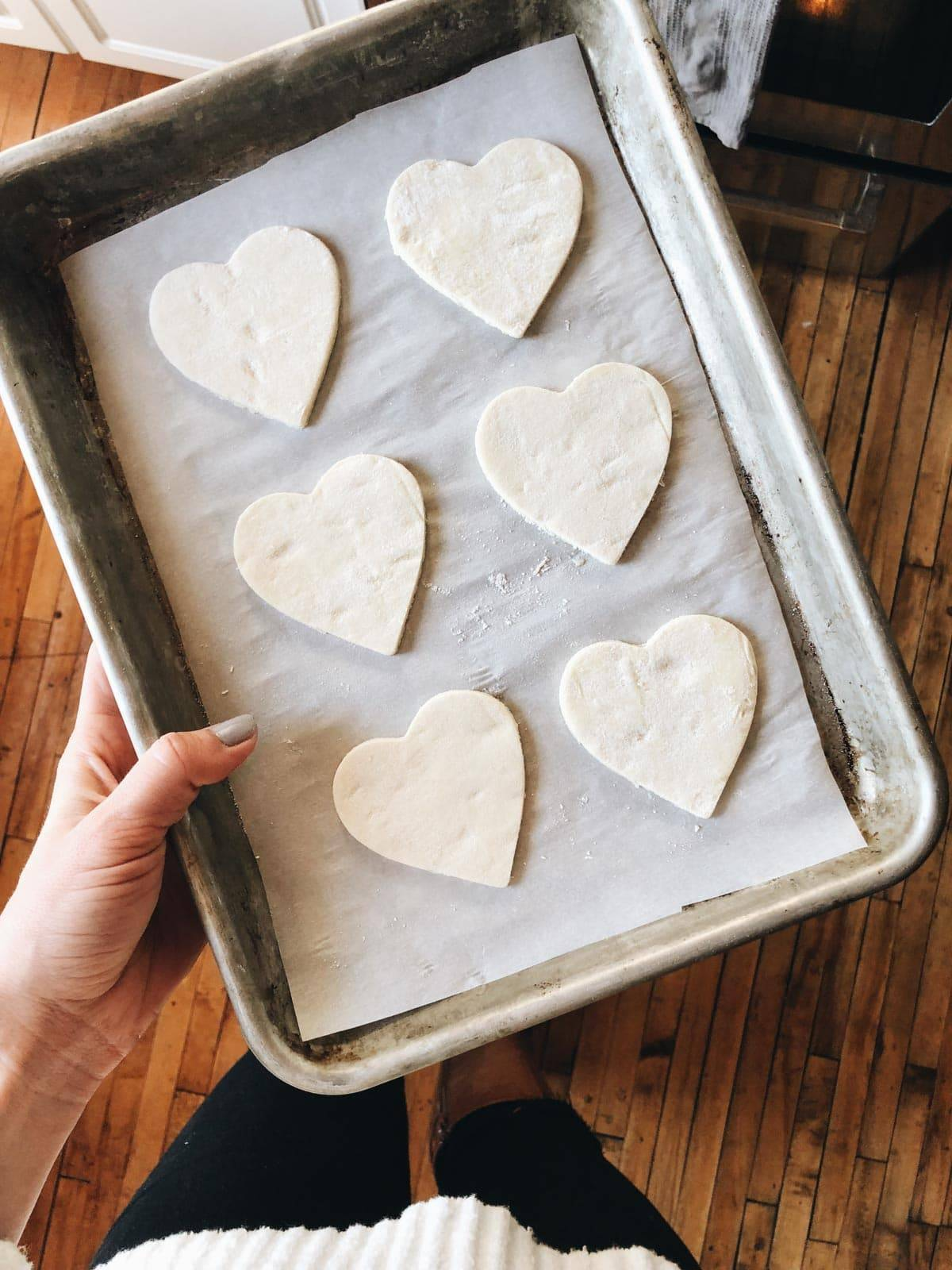 Puff pastry in heart shapes on pan before baking.