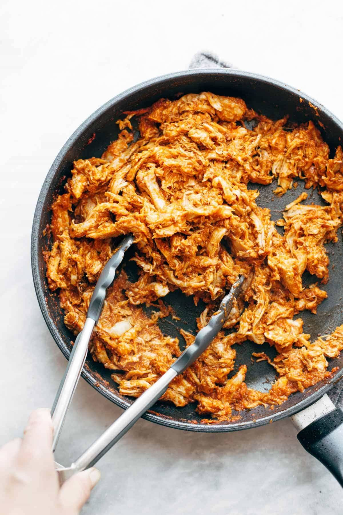 Chicken Tinga in pan with tongs.