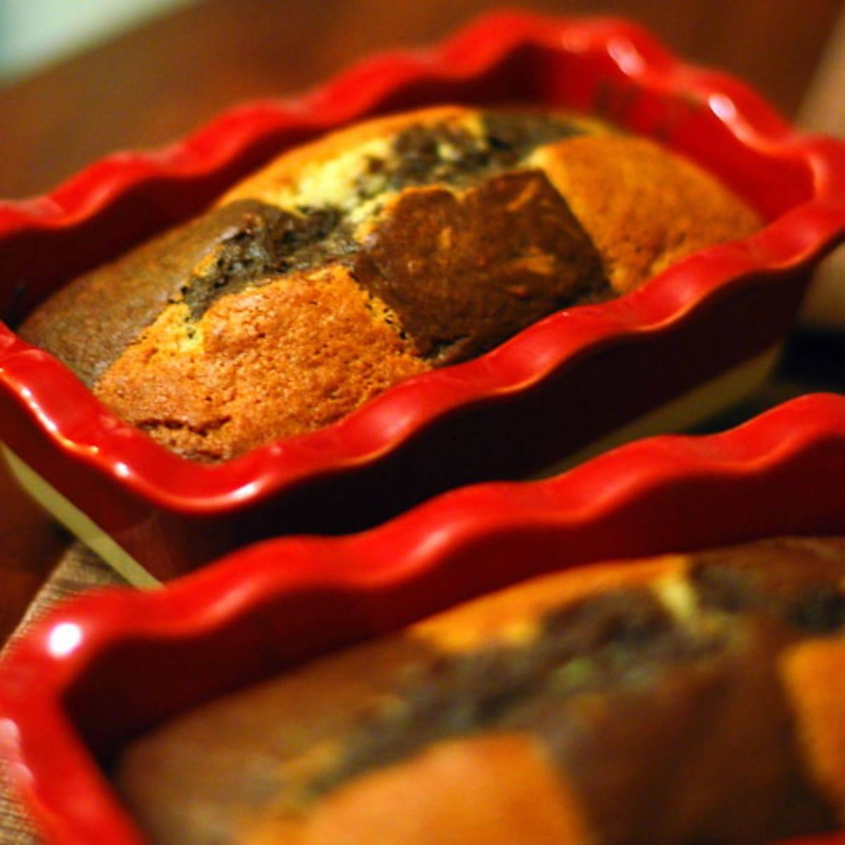 Two loaves of chocolate checkered banana bread in red baking dishes.
