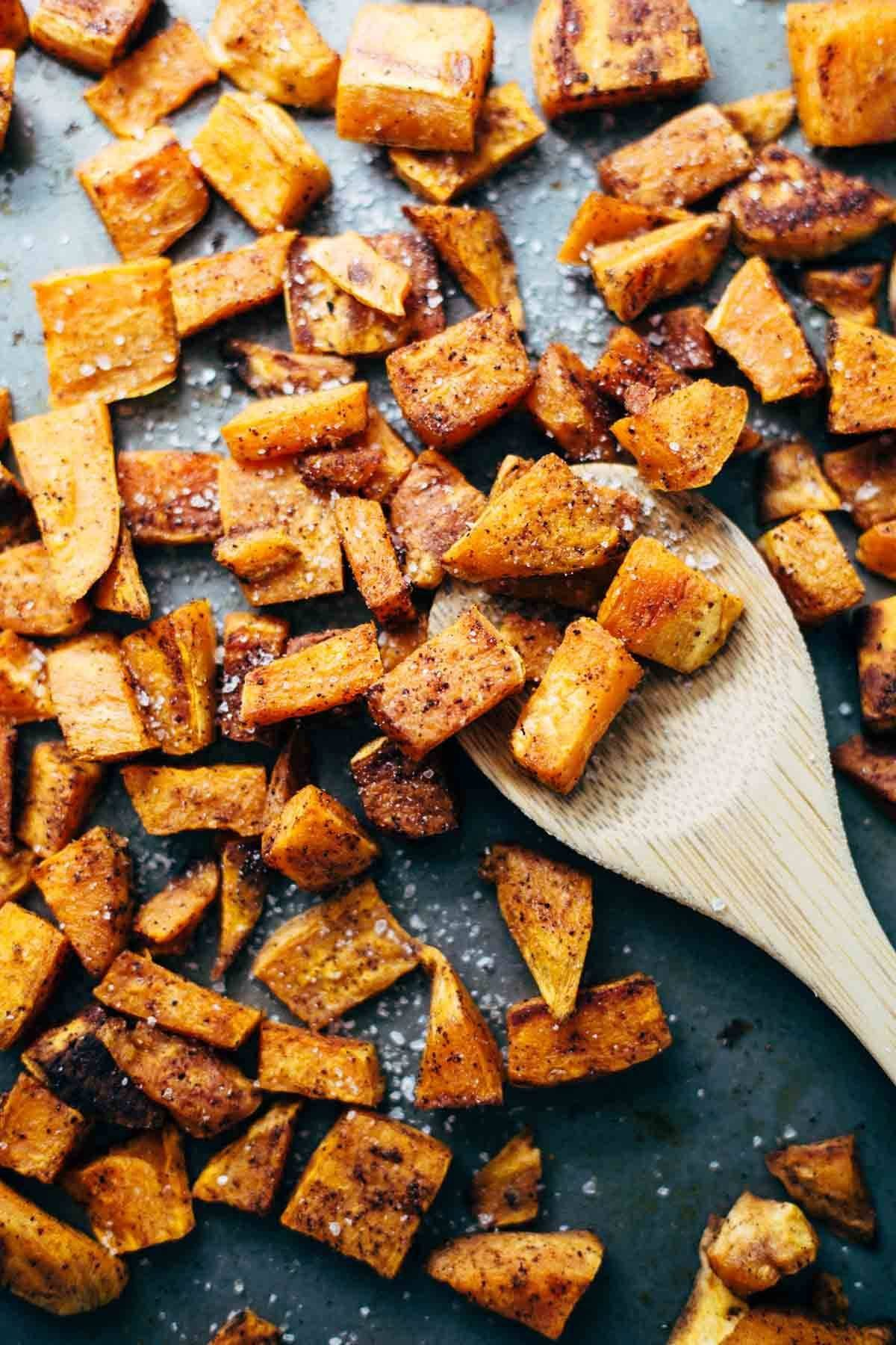 Roasted sweet potatoes on a wooden spoon.