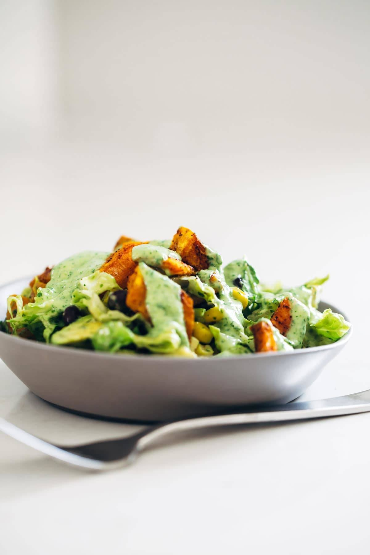 This healthy Spicy Southwestern Salad recipe has roasted sweet potatoes, black beans, corn, lettuce, and creamy avocado dressing! | pinchofyum.com