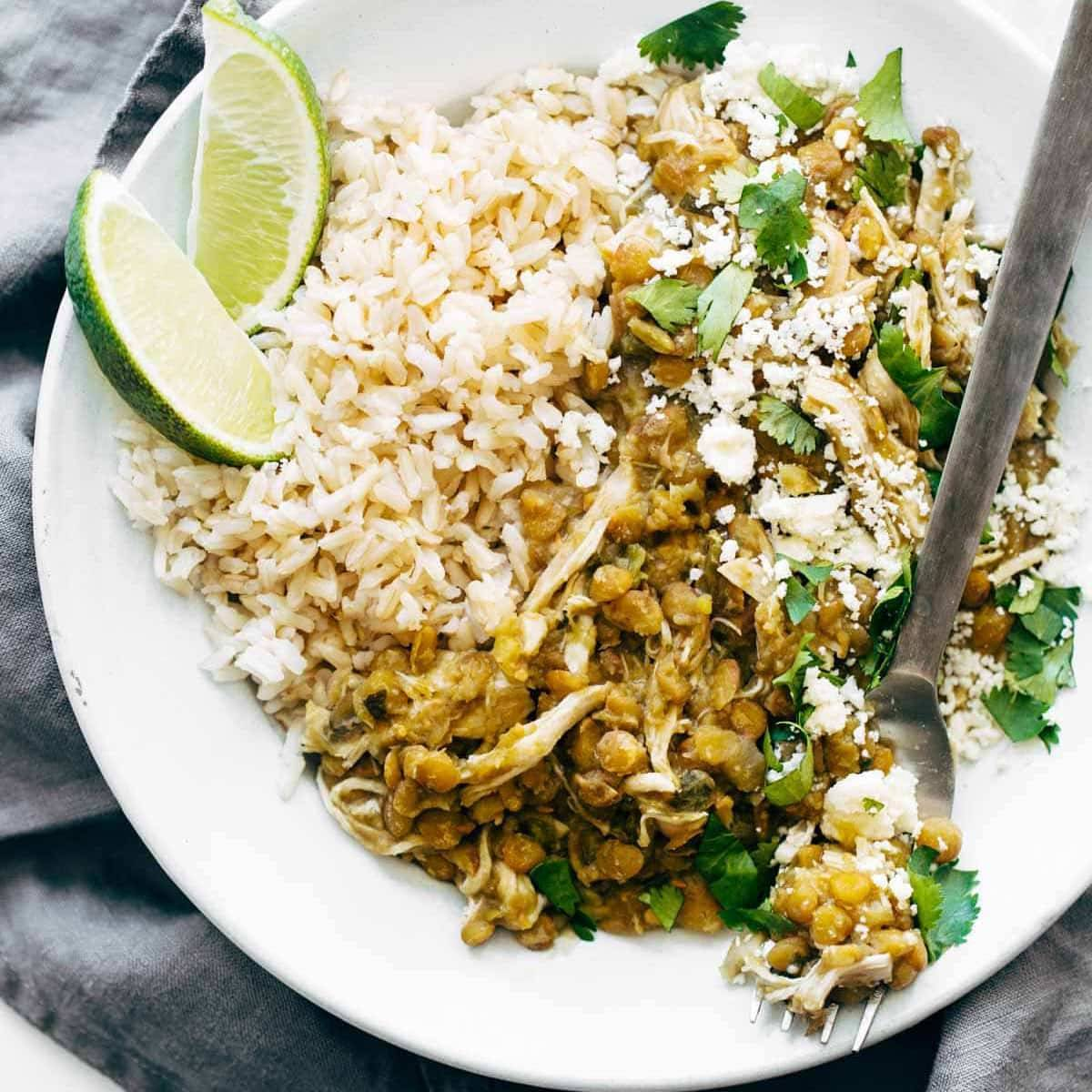 White rice and lentils with shredded chicken, fresh cilantro and quartered lime slices.