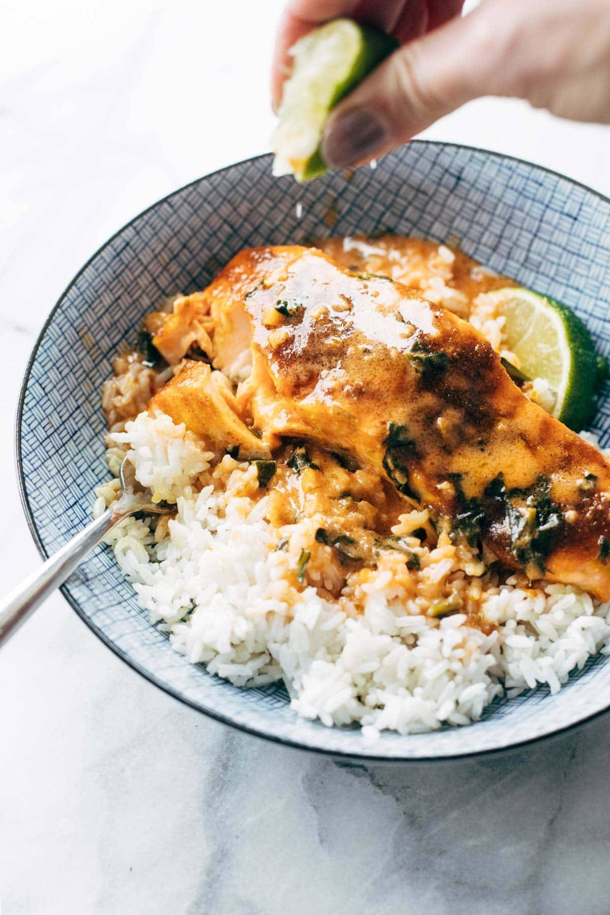 Squeezing lime over coconut curry salmon.