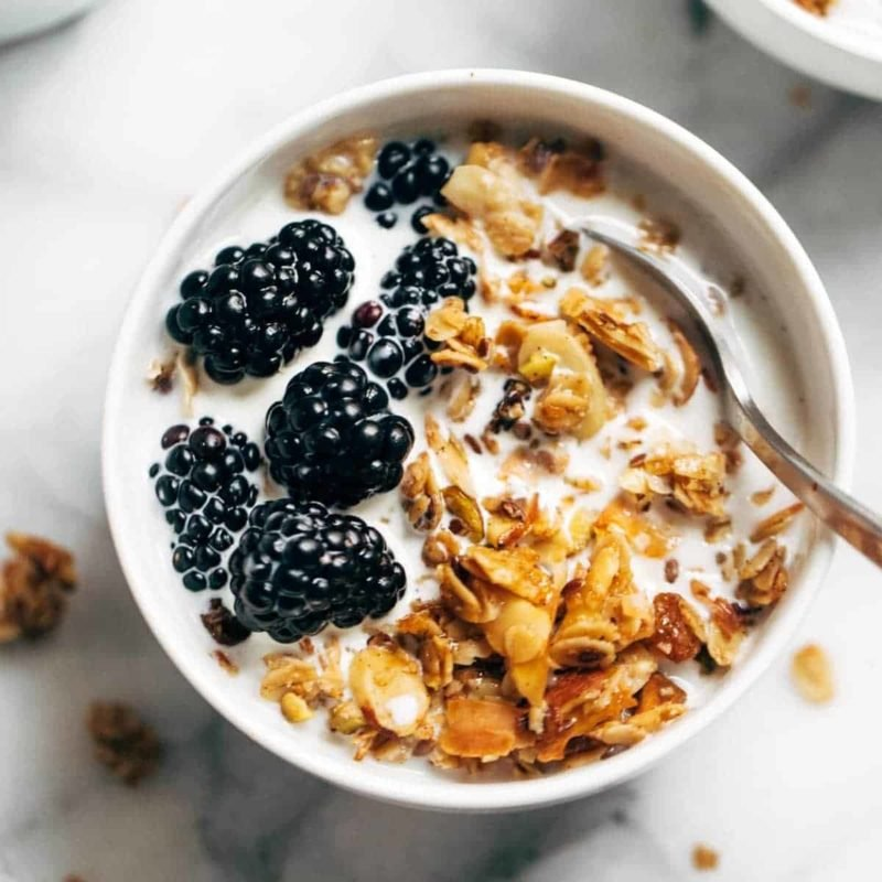 A bowl full of coconut oil granola and berries with a spoon in it.