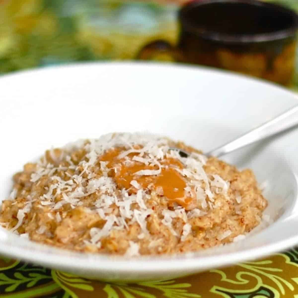Coconut peanut butter oatmeal with coconut shreds in a bowl with a spoon.