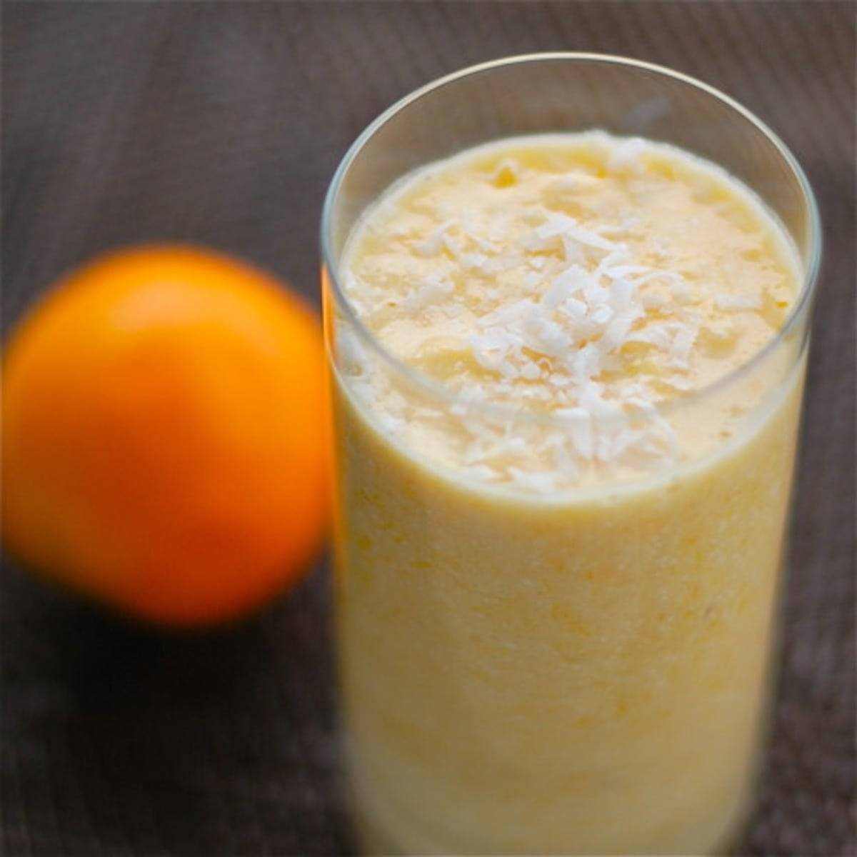 Coconut pineapple orange smoothie in a glass next to an orange.