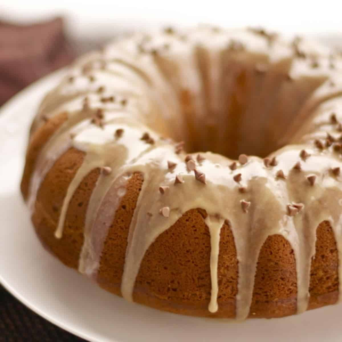 Coffee streusel bundt cake on a plate with drizzle.