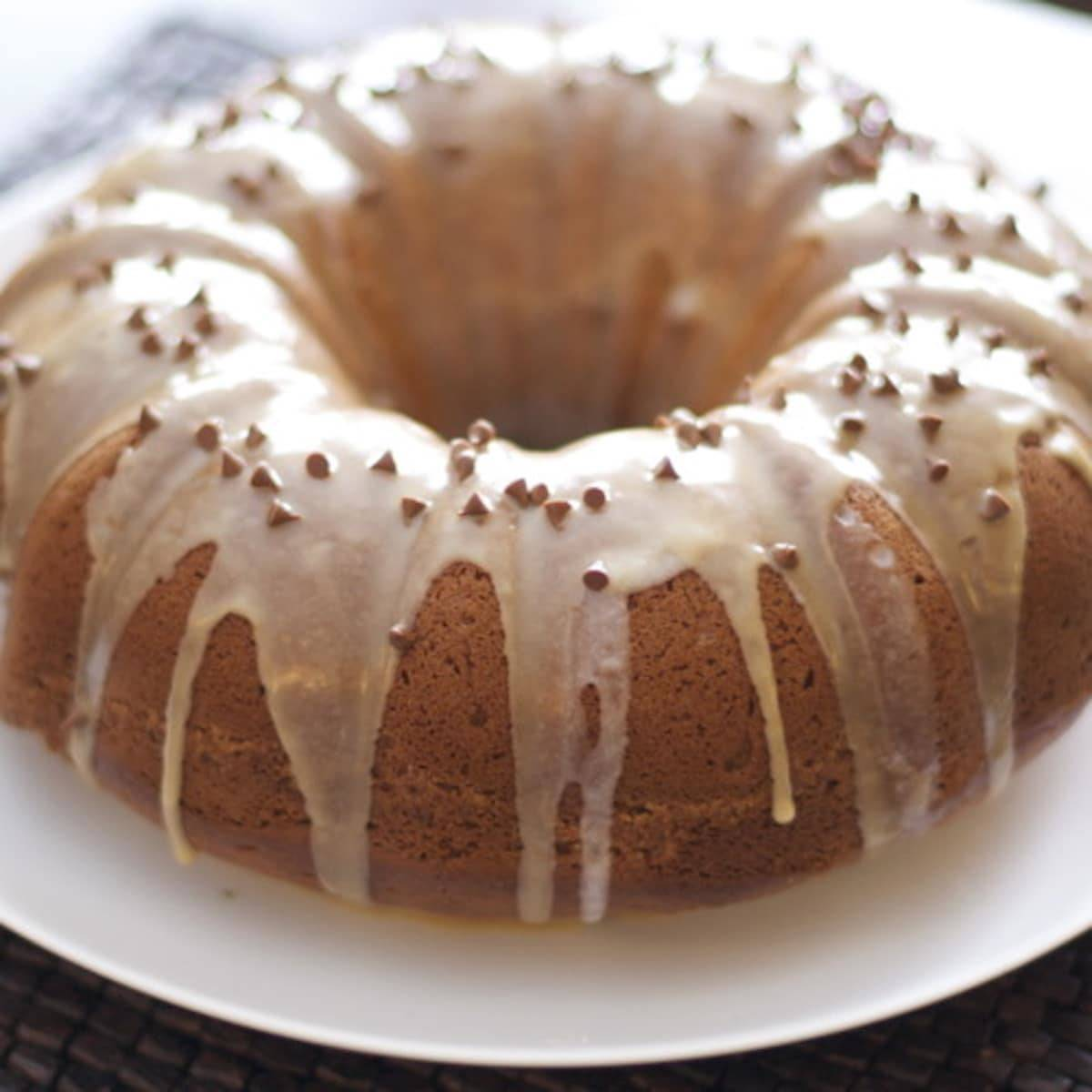 Coffee streusel bundt cake on a white plate with drizzle.
