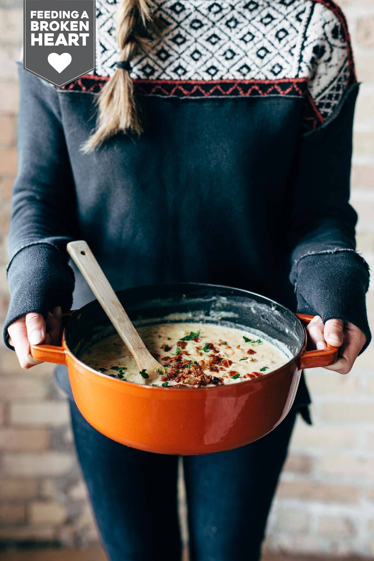 Woman holding a pot of Creamy Potato Soup.