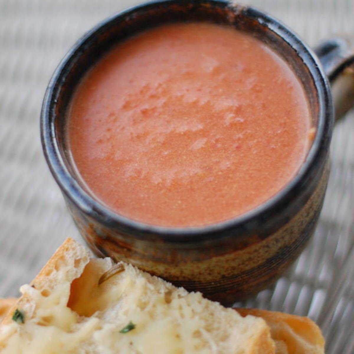 Creamy tomato balsamic soup in a mug next to a piece of bread.