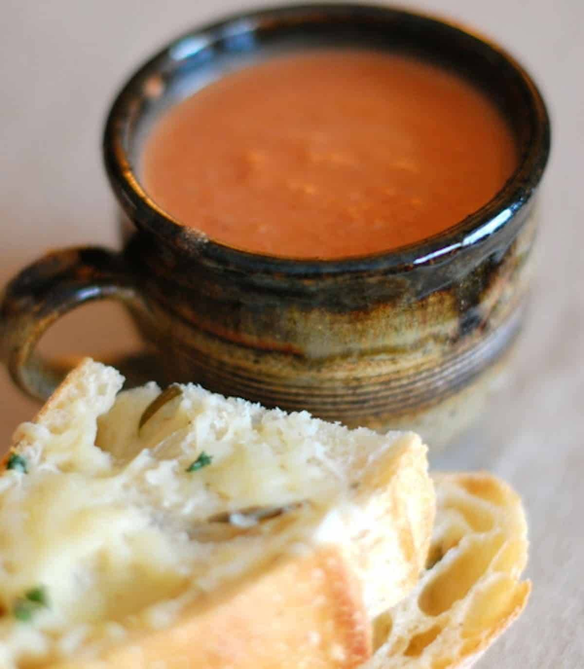 Creamy tomato balsamic soup in a mug with pieces of bread.