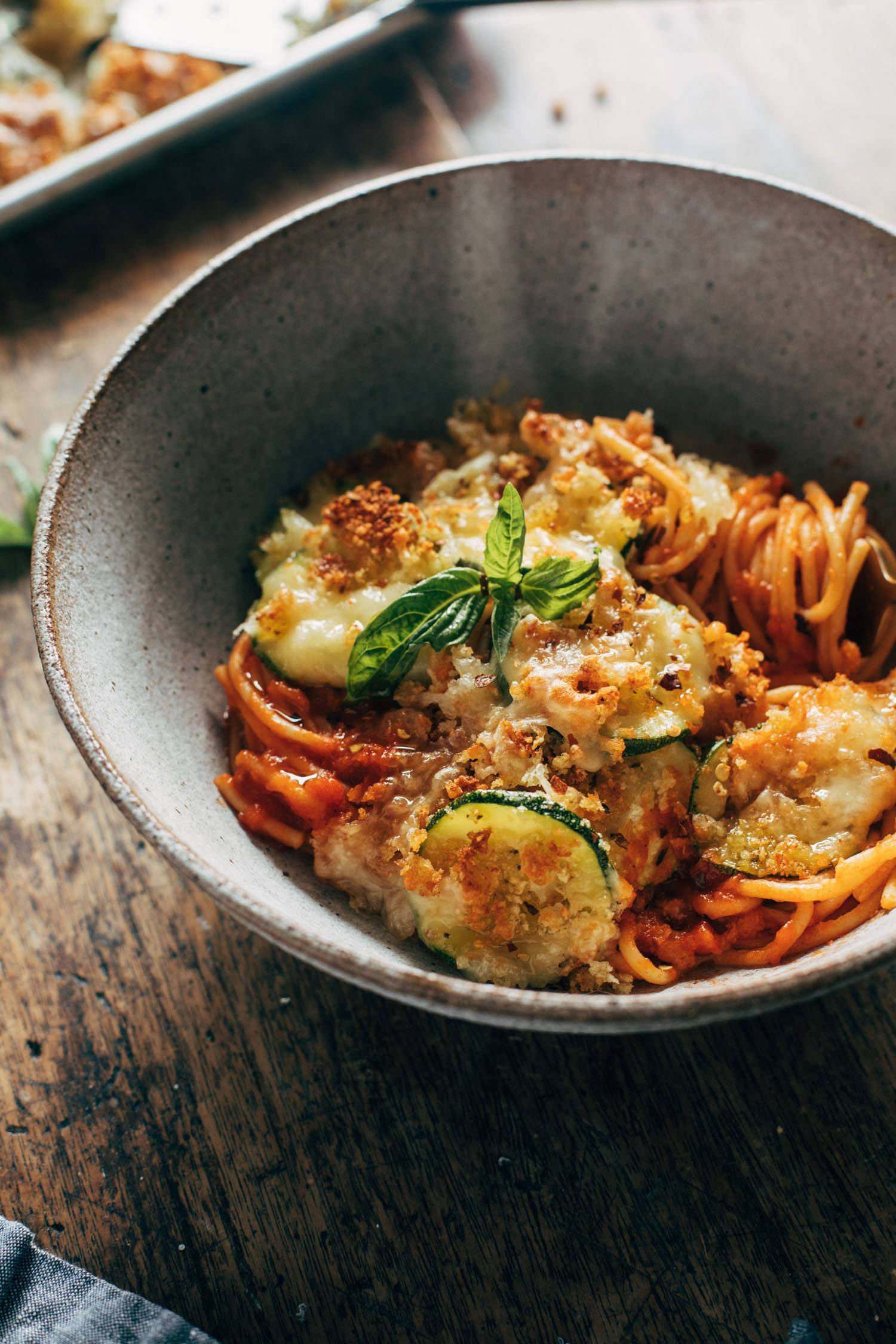 Spaghetti with crispy zucchini in a bowl with melted cheese and fresh basil on top.