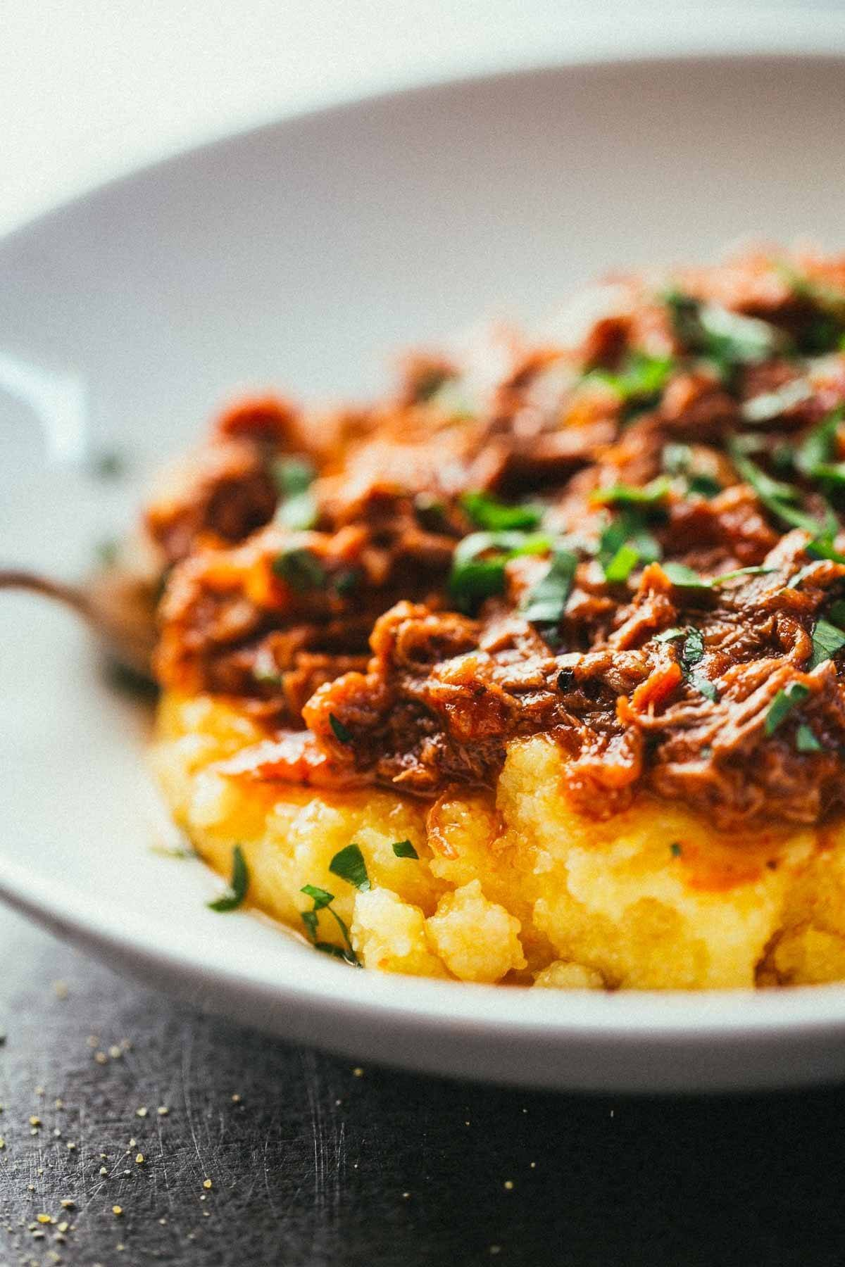 Crockpot Braised Beef Ragu with Polenta on a white plate.