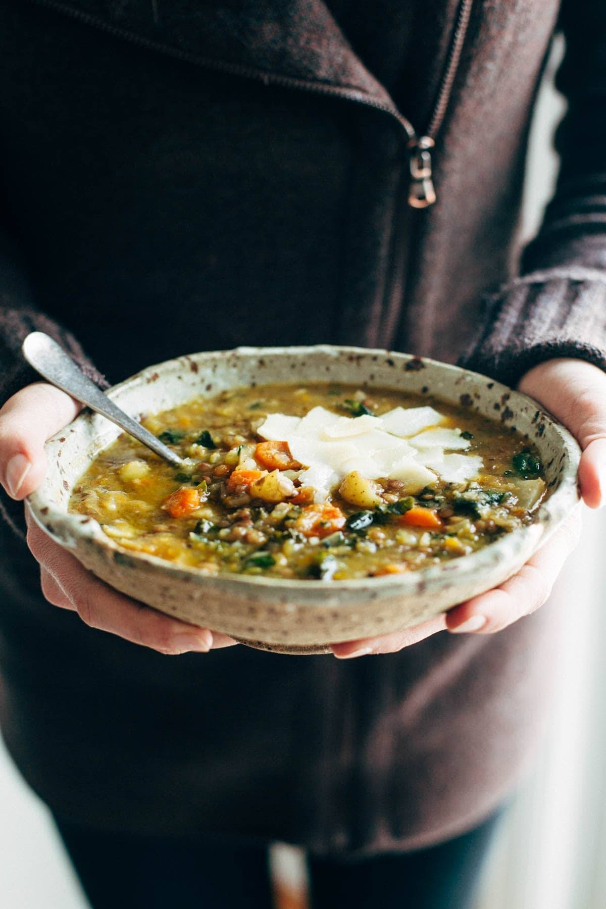 person holding lentil soup in a bowl with a spoon
