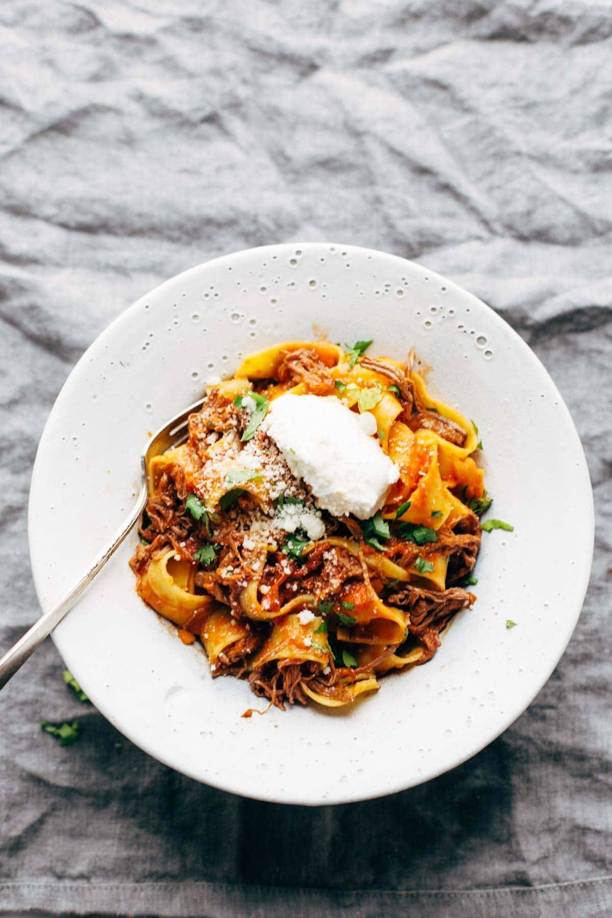 Slow Cooker Beef Ragu with Pappardelle in a bowl with ricotta.