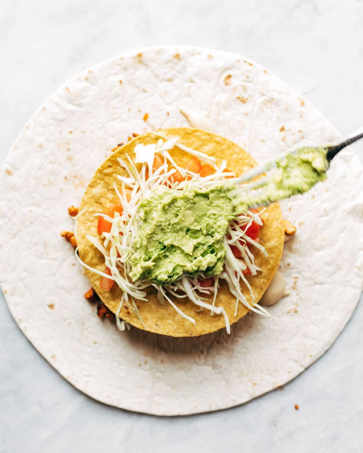 Adding guacamole to vegan crunchwrap supreme.