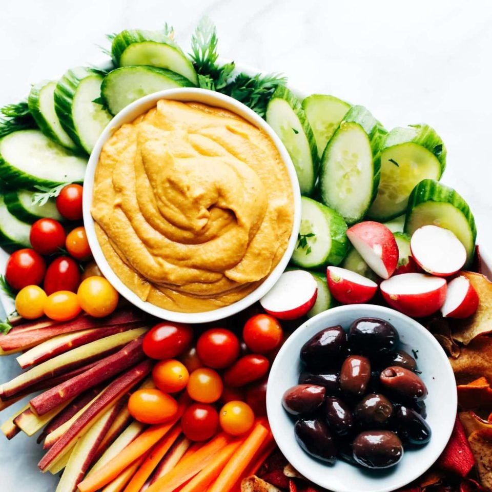 Curry Hummus on serving platter with vegetables and olives.