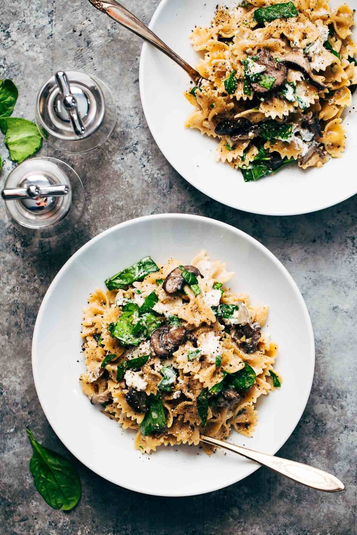 Mushroom Pasta With Goat Cheese In Two White Bowls Forks