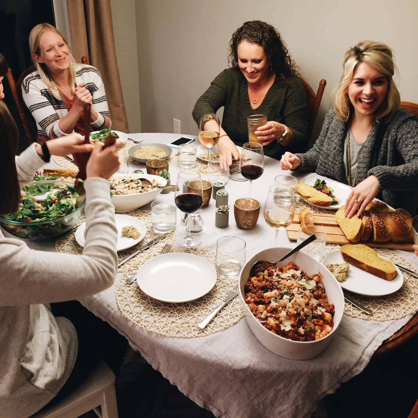 Table with plates of food and women laughing.