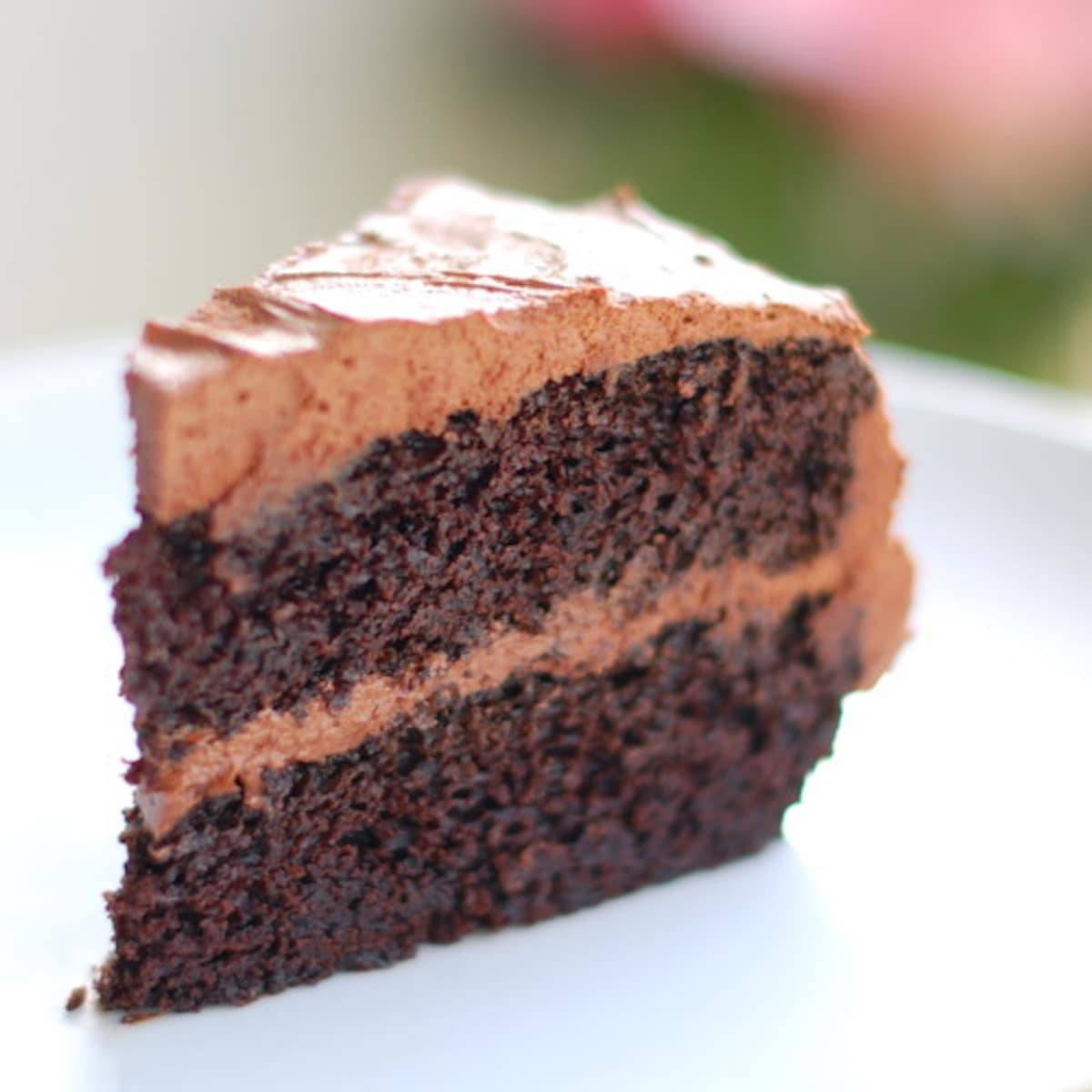 Slice of double chocolate cake with buttercream frosting.