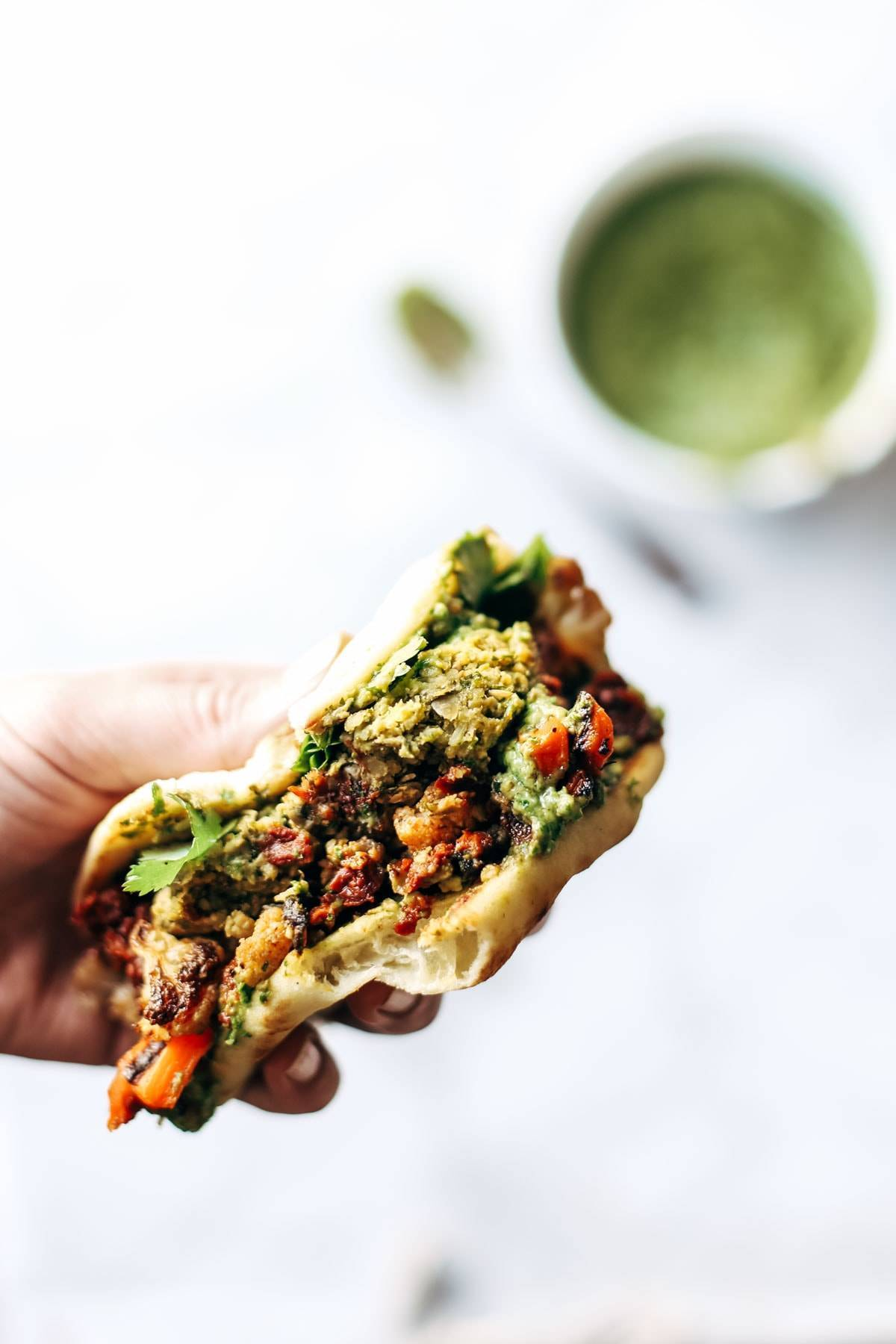 Naan-wich: 5 ingredient falafel, roasted veggies, and avocado sauce stuffed between pillowy garlic naan. Best sandwich recipe I've ever made. | pinchofyum.com