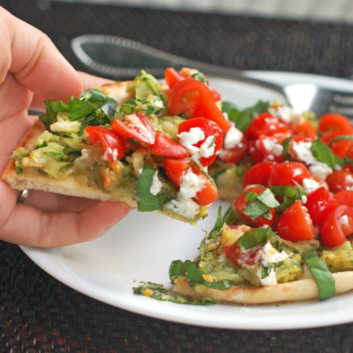 Flatbread pizza with zucchini, cherry tomatoes, and basil.