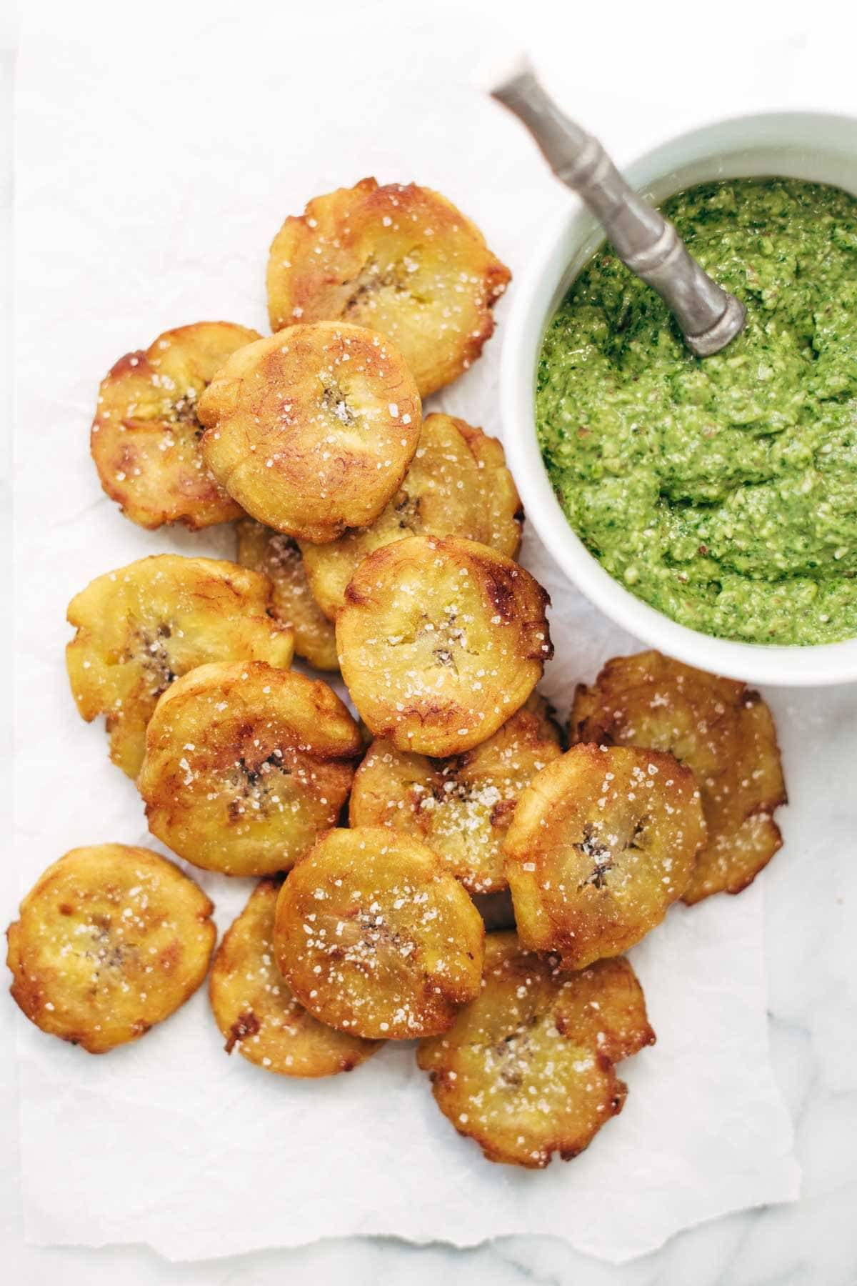 Crispy Salted Tostones with a bowl of green sauce.