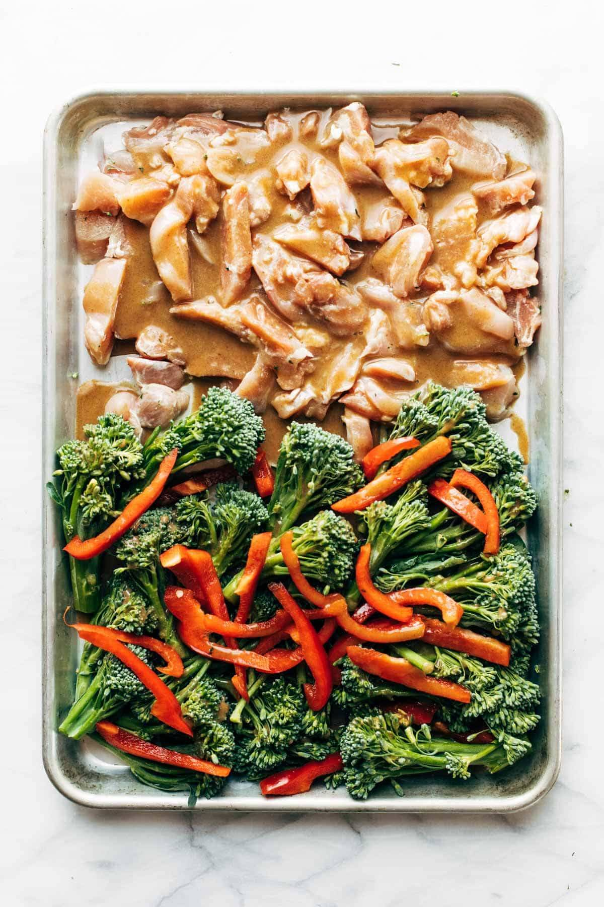Raw chicken and veggies on a sheet pan.