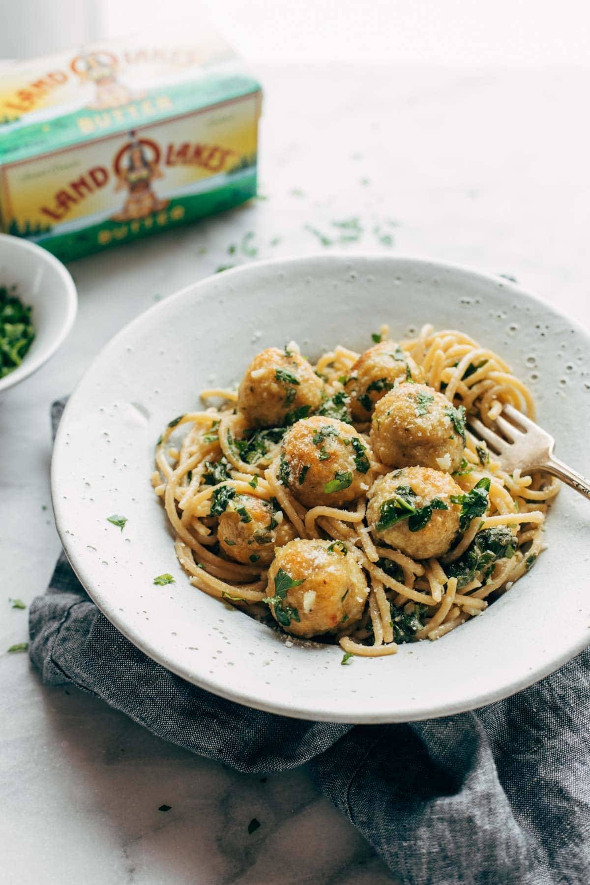 Garlic Herb Spaghetti with Baked Chicken Meatballs in a bowl with fork twirl.